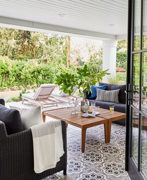 Another view of Emily Henderson's beautiful, Moroccan-themed patio. Say hello to the stately Calo sofas, grounding that beautiful tiling.
