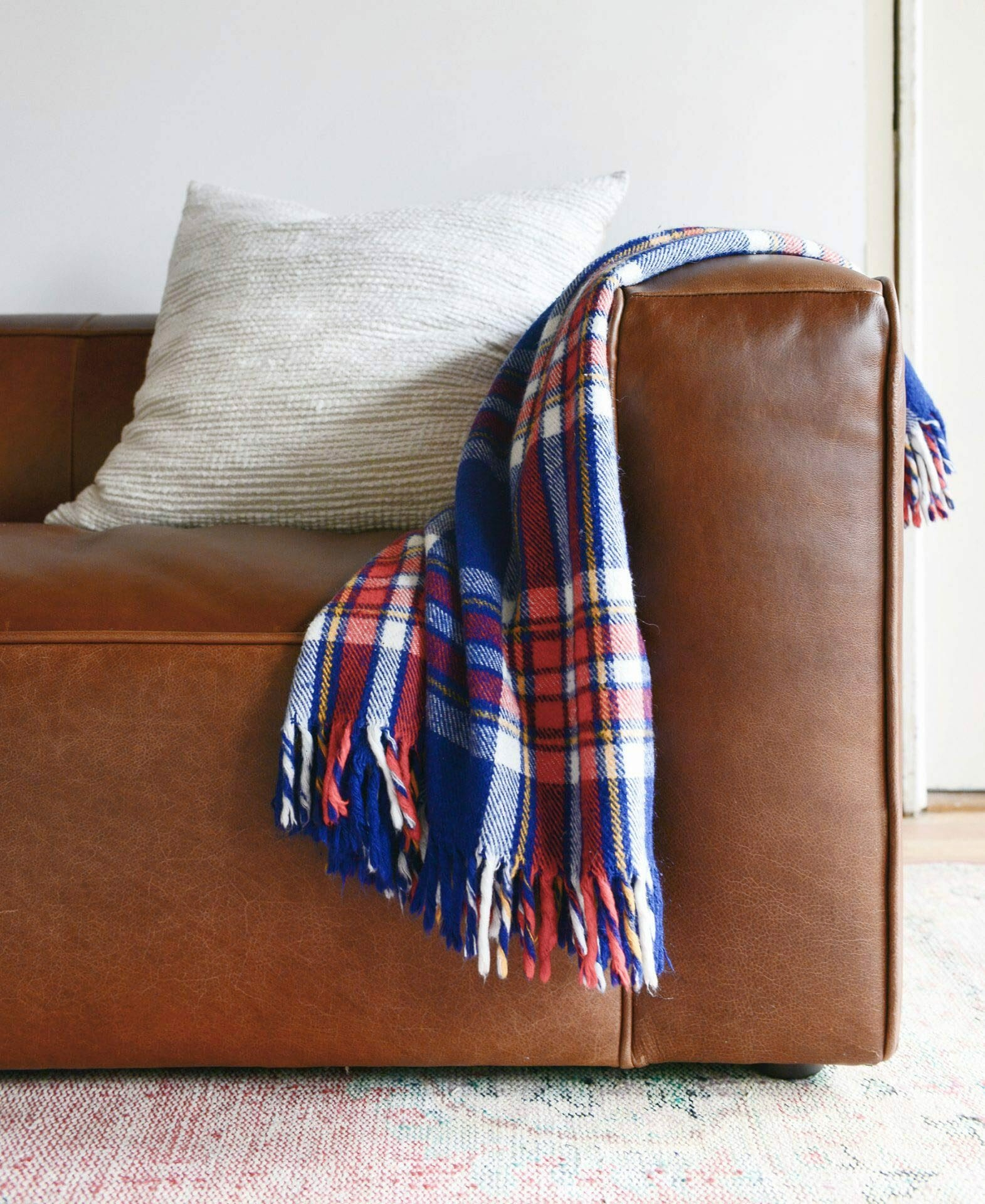 A plaid throw is draped over an Article leather sofa from Yellow Brick Home