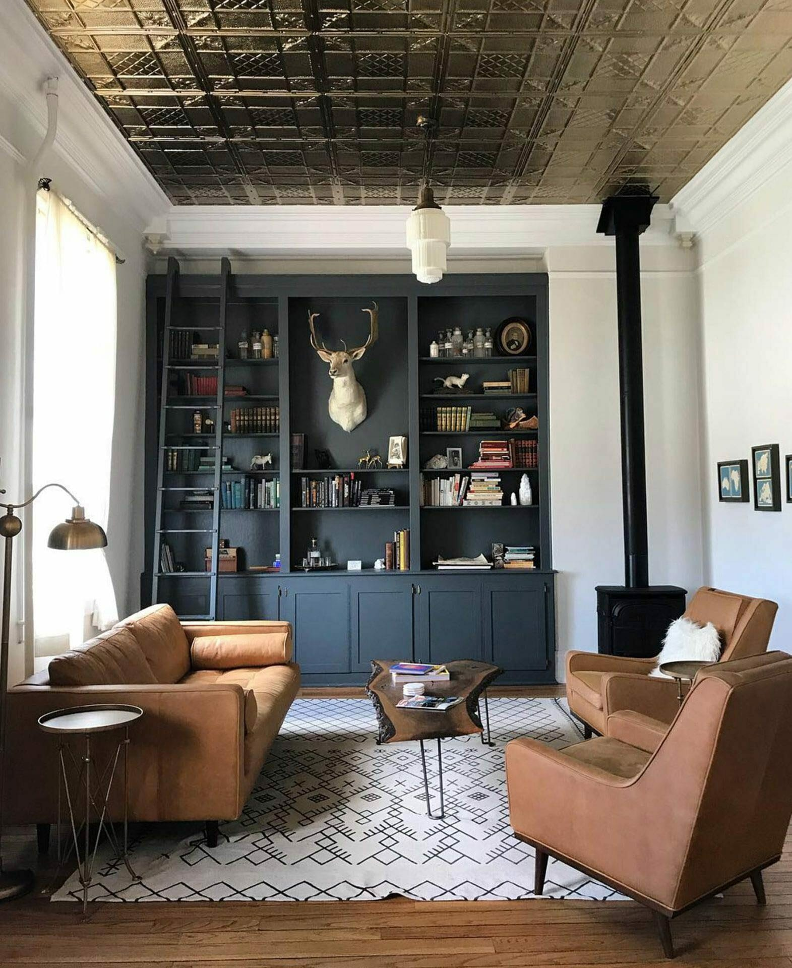A living room featuring an Article leather sofa and two leather chairs from Dram Apothecary
