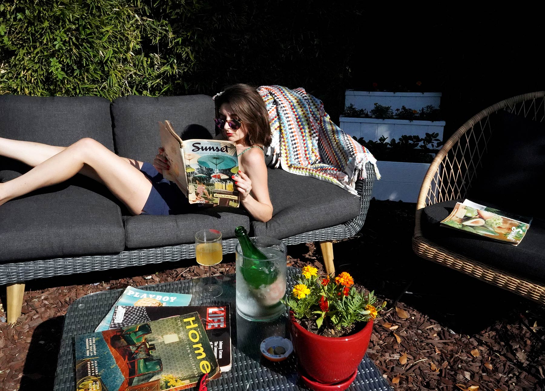 Marissa A. Ross reads a magazine on her Article Ora sofa after a day of outdoor entertaining.