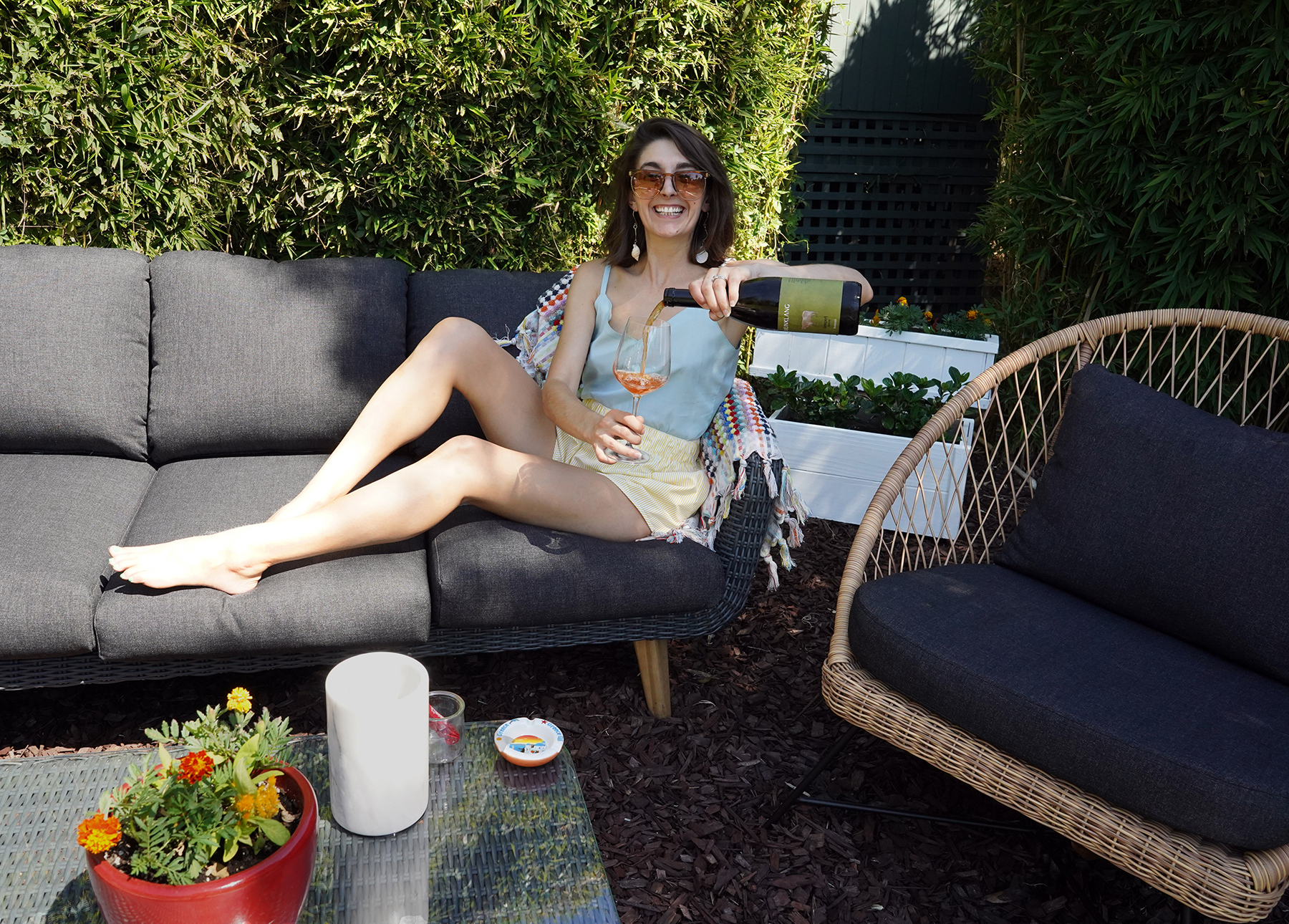 Marissa A. Ross pours a glass of wine while relaxing on her Ora outdoor sofa.