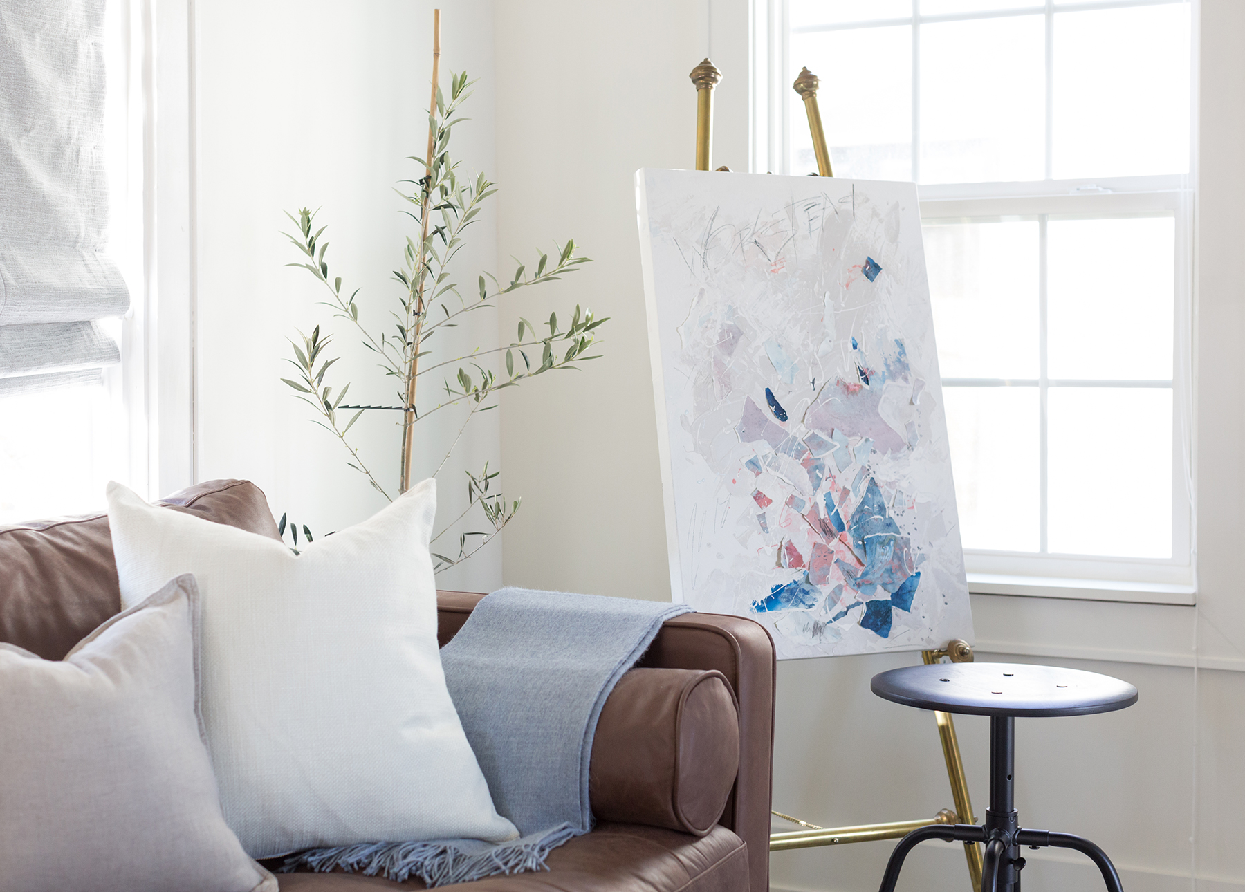 The Makerista's living room, with a Sven Chocolat sofa and artwork on an easel.