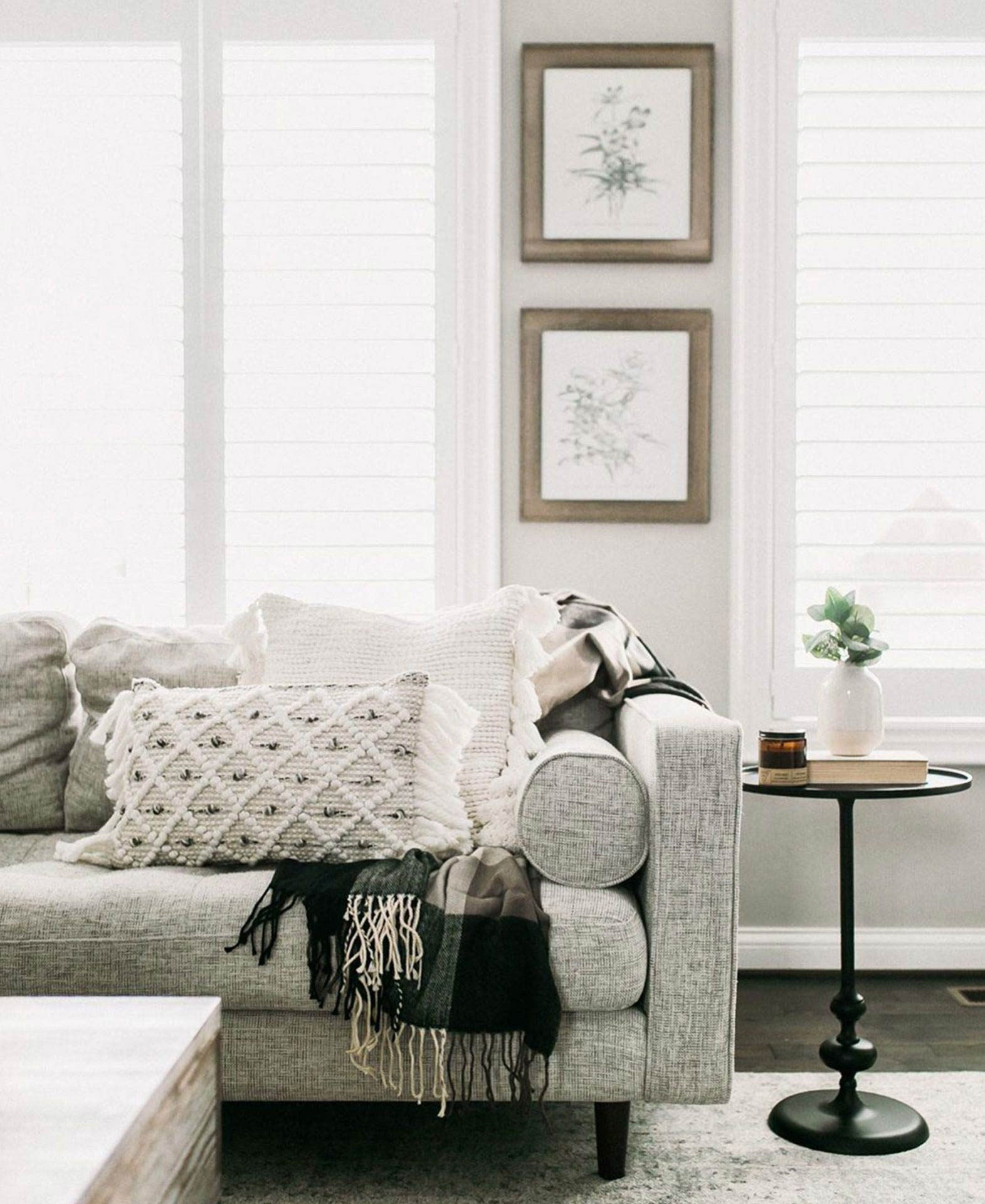 A Sven Birch Ivory fabric sofa is draped with throws and throw pillows in the home of blogger Our Dwelling Place.