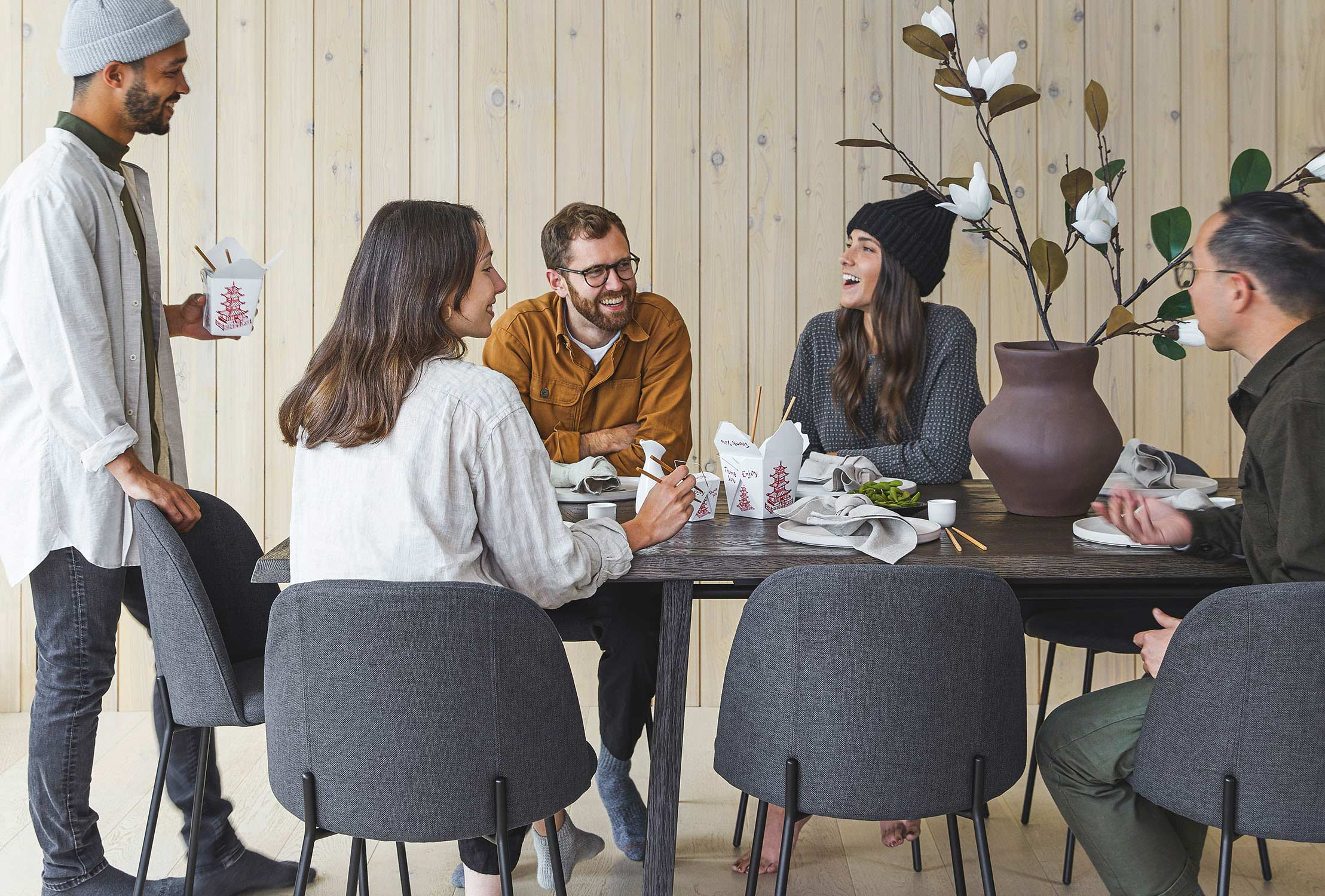 Cute people in toques gather around a dark wood table. Some are standing, most are seated in gray upholstered chairs.