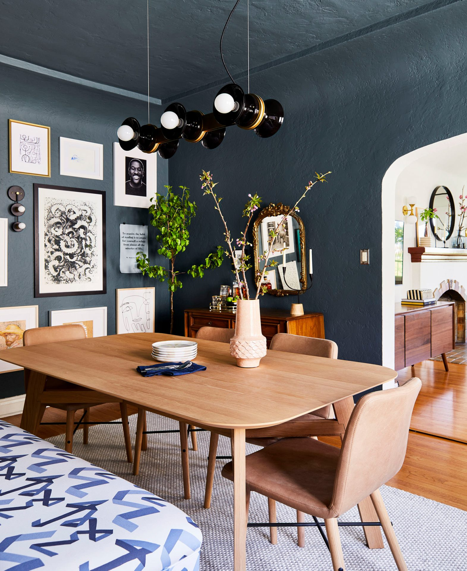 Emily Henderson designed this dining room with dark teal walls, leather Article chairs, and a light wood table.