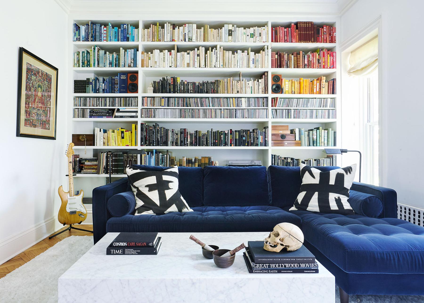 How to clean a velvet sofa: Blue velvet Sven sofa in front of colorfull bookshelves.