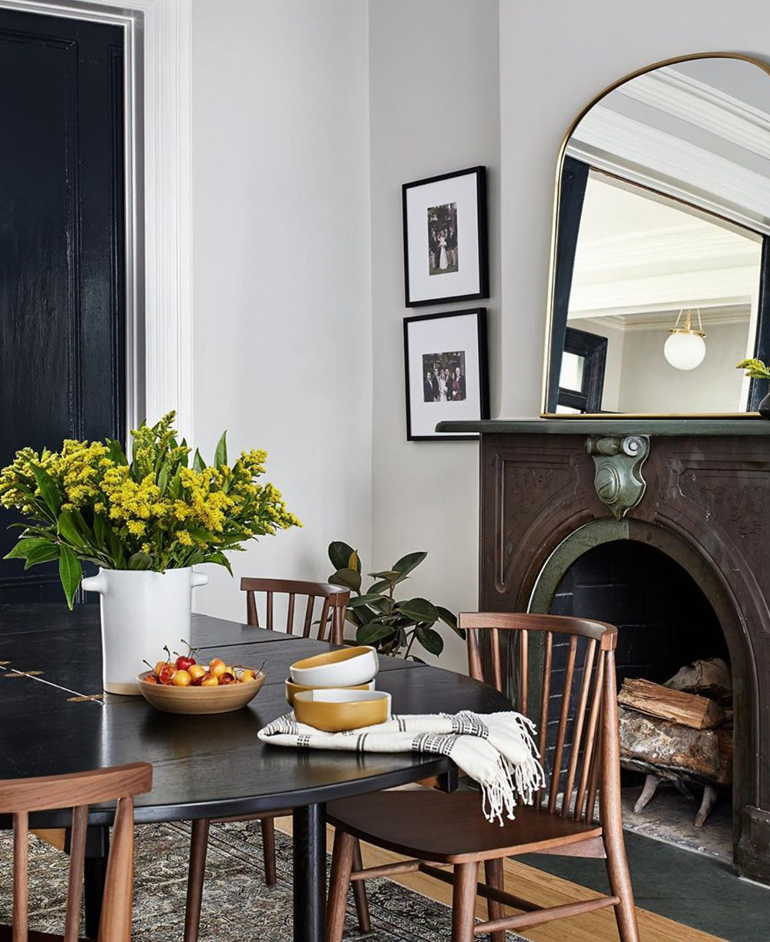 Interior designers from Sanabria and Co show a dining room with Article dining chairs and a rustic fireplace.