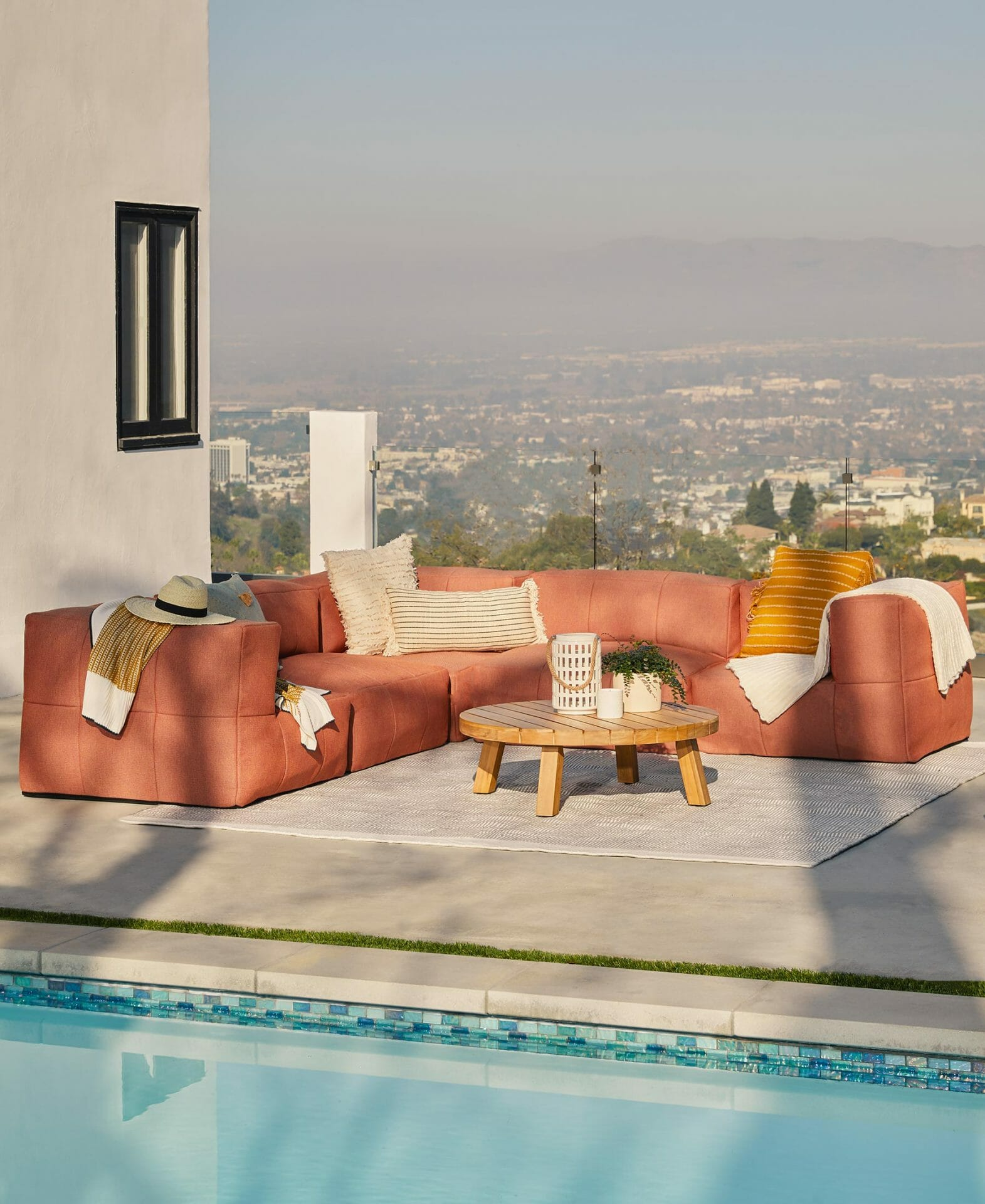 The Corvos Sectional in Terracotta is set up beside a pool.
