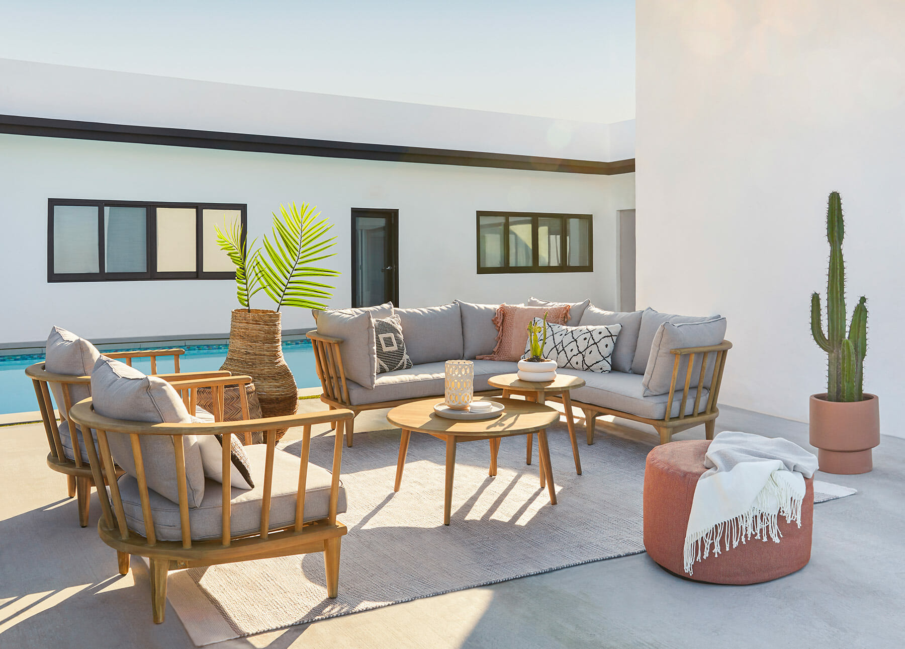 The Sora sectional and lounge chairs sit poolside.