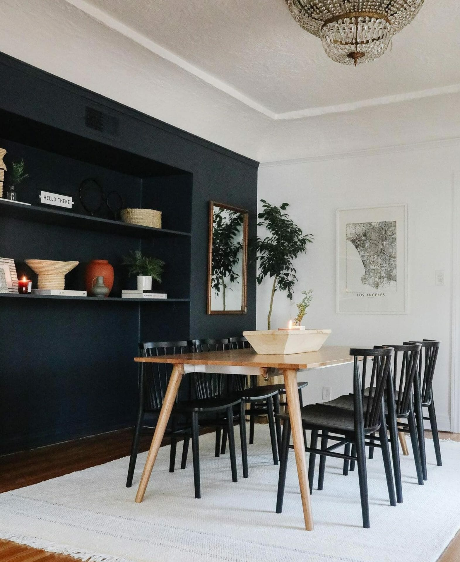 A dining room features neutral tones and a black accent wall.