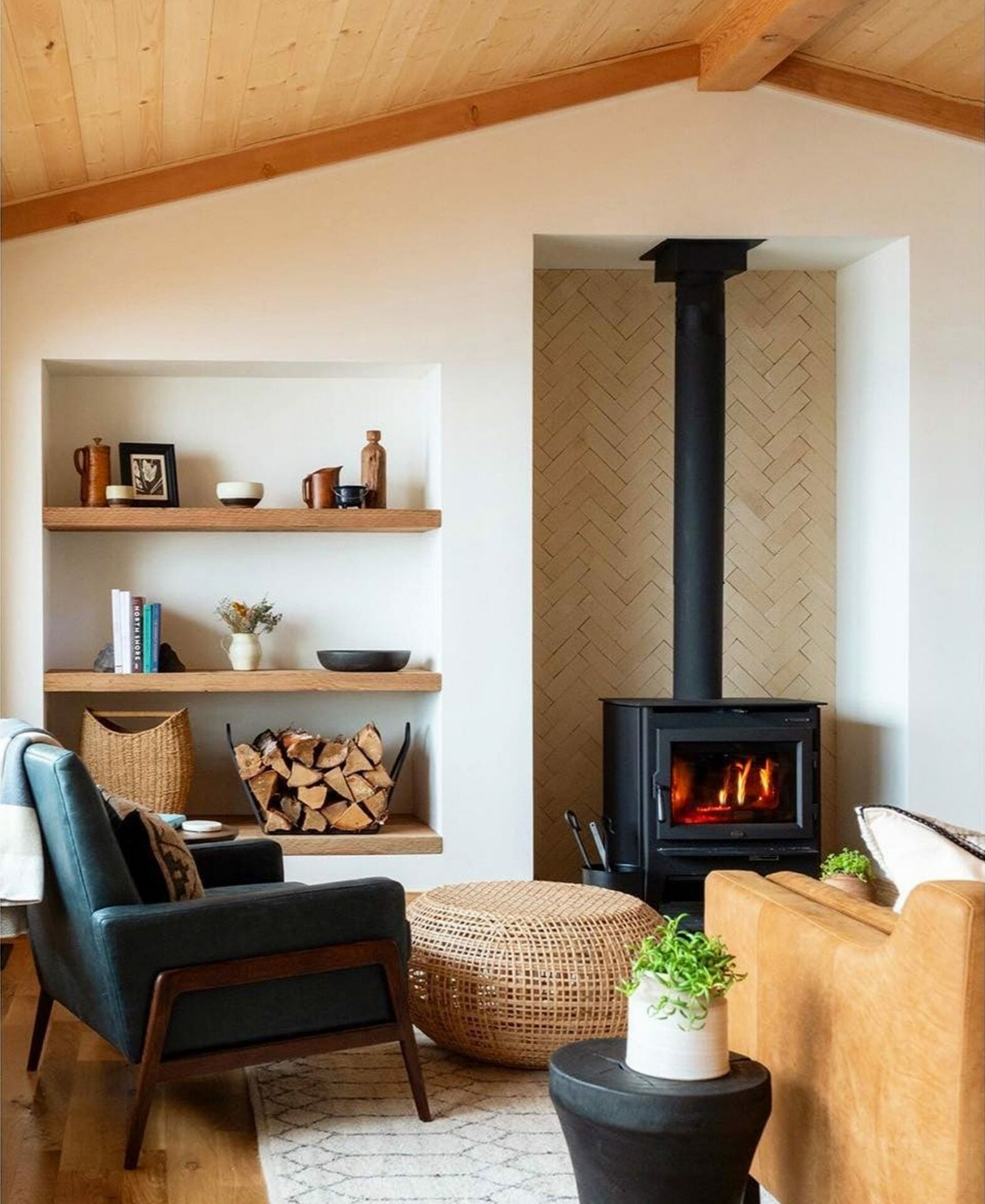 Two armchairs are turned towards a black fireplace in a cozy living room.