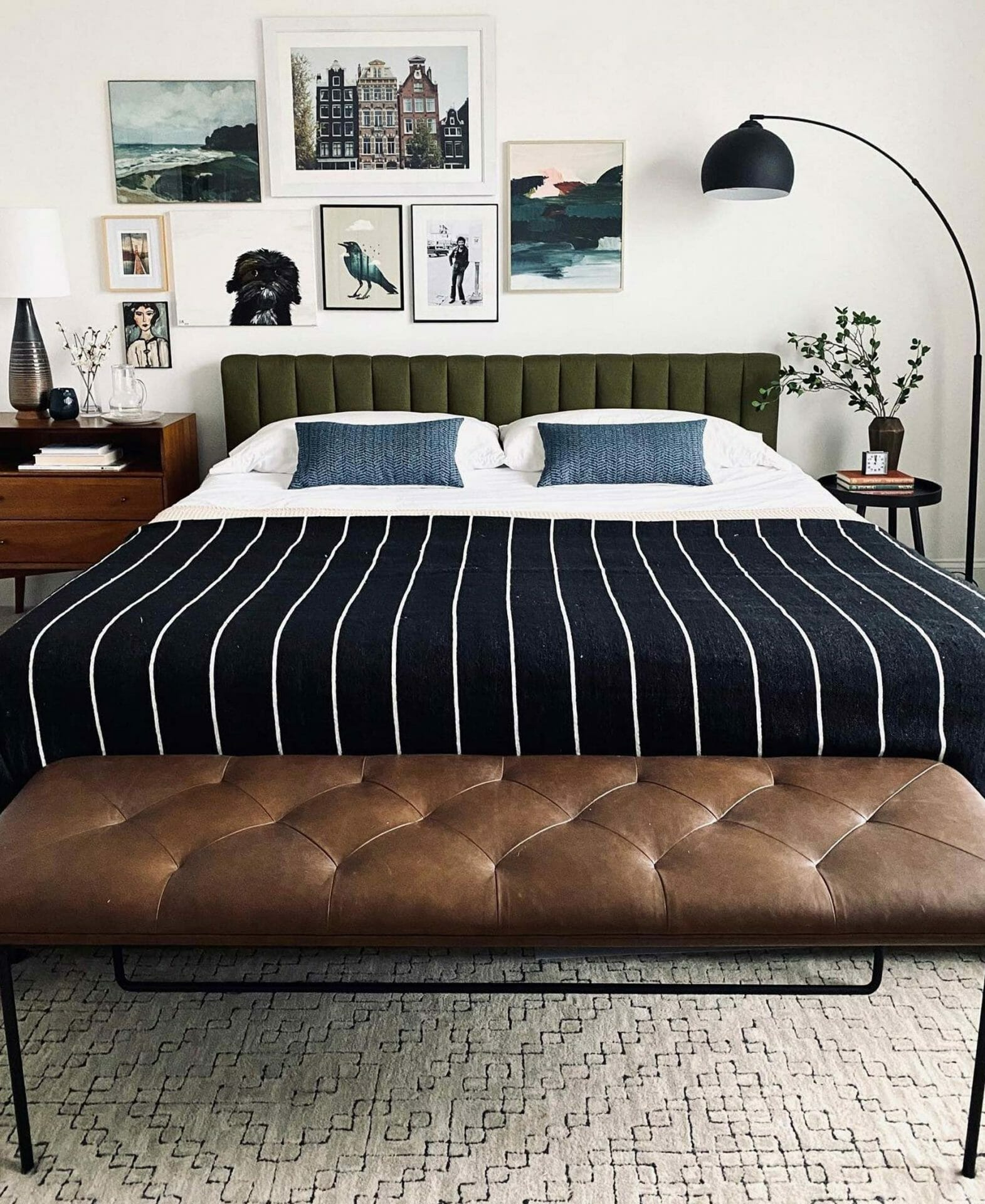 A bedroom with a queen sized bed and brown Article Level Bench is shown.