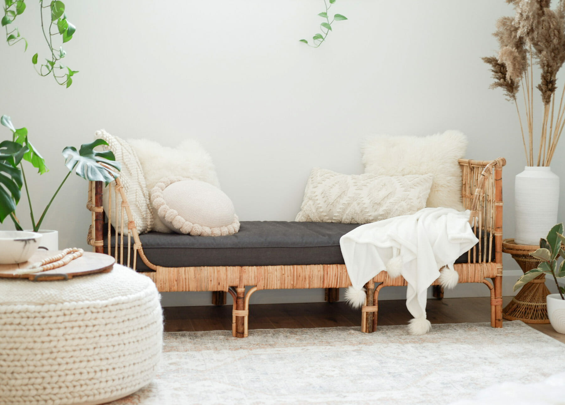 Article's rattan Sol Daybed is adorned with cream colored pillows and a throw.