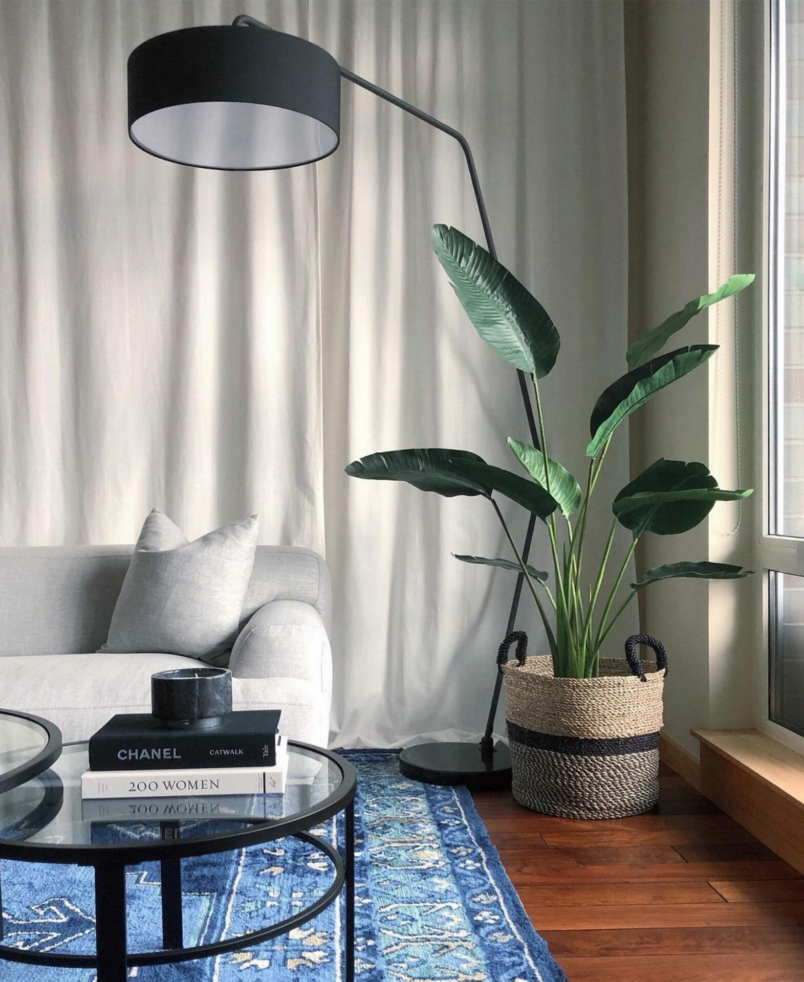 Eclectic Prodigy's living room features a bright blue rug, white sofa, palm plant, and black Article floor lamp.