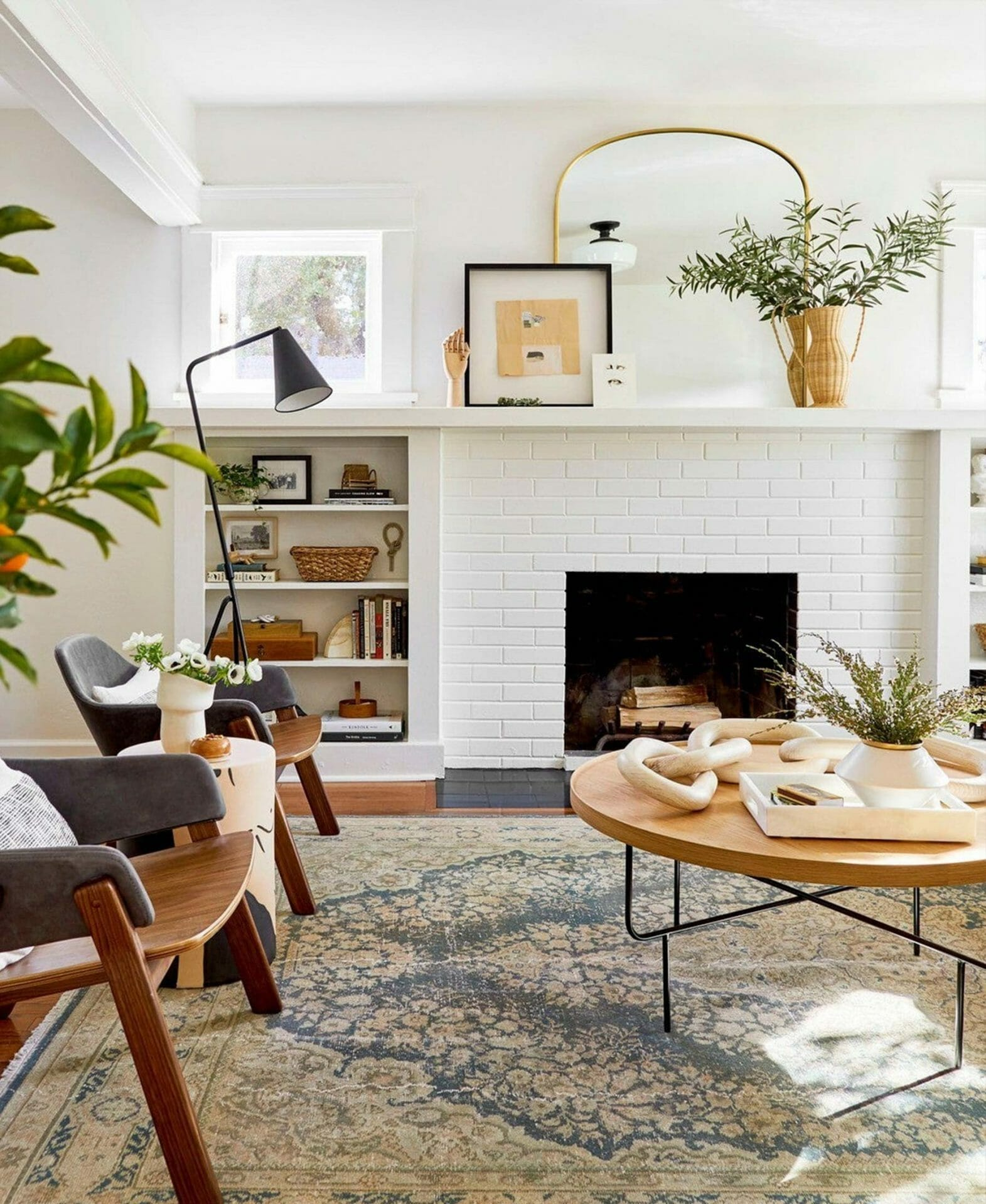 This living room designed by Emily Henderson features a white fireplace and Gira Lamp.