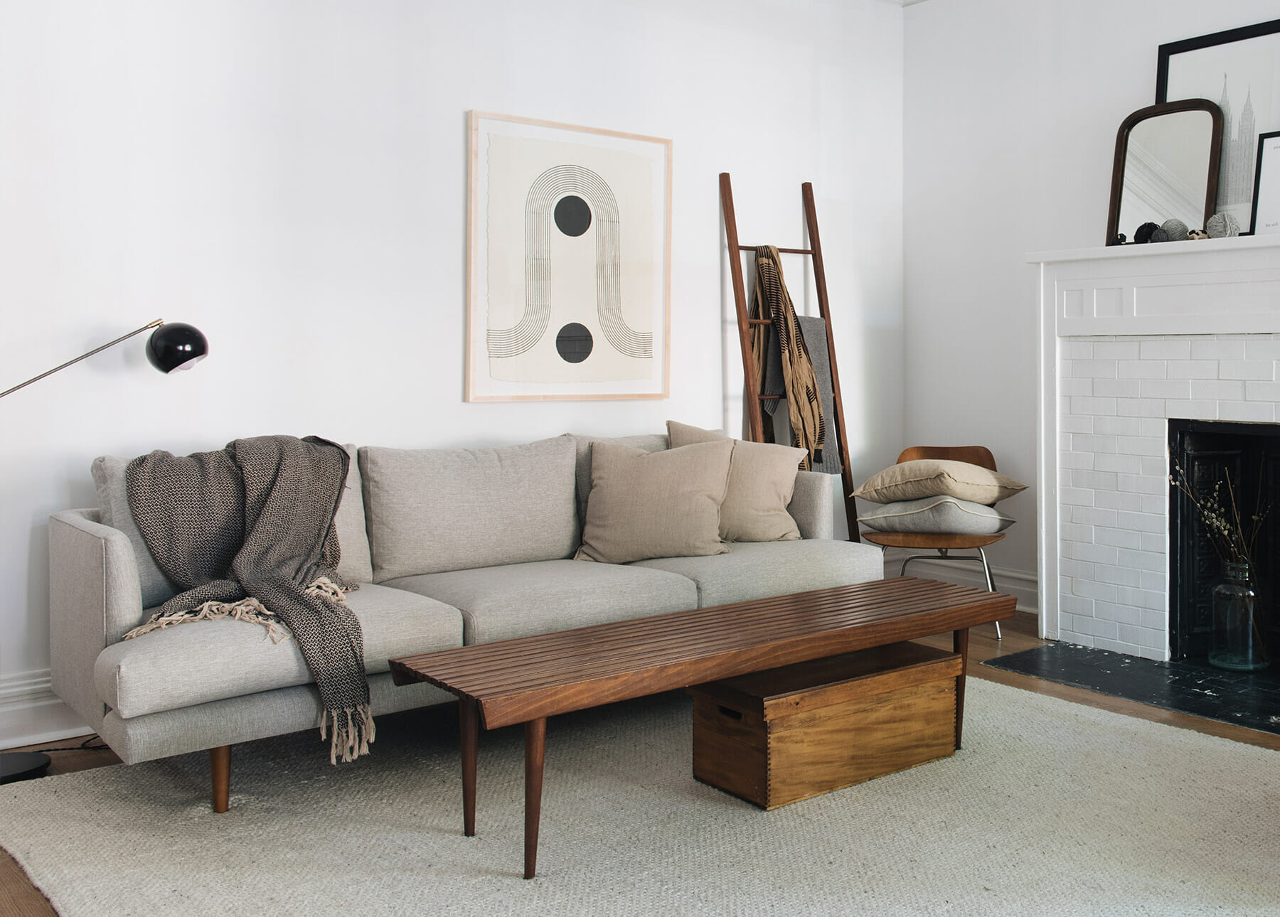 An Article minimalist sofa is in a living room with a piece of geometric art and a blanket ladder.