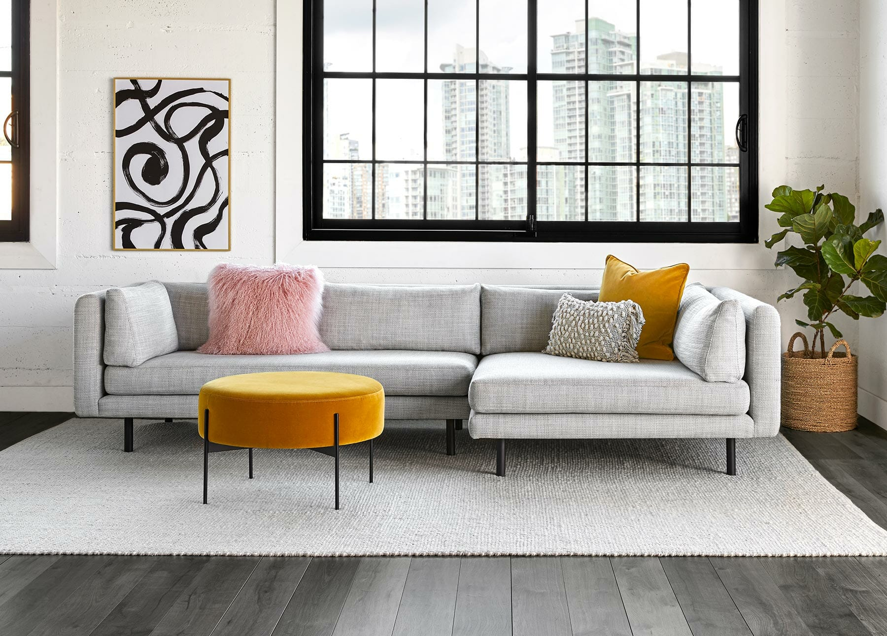 Article's Lappi Sectional in a light gray sits next to a yellow ottoman and black and white print.