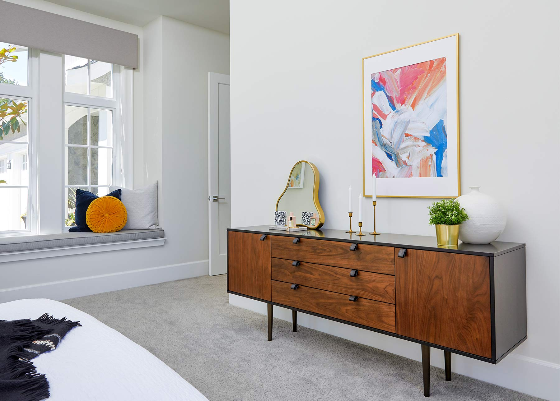 The Envelo Sideboard is shown in a modern bedroom with colorful artwork and an oblong mirror.