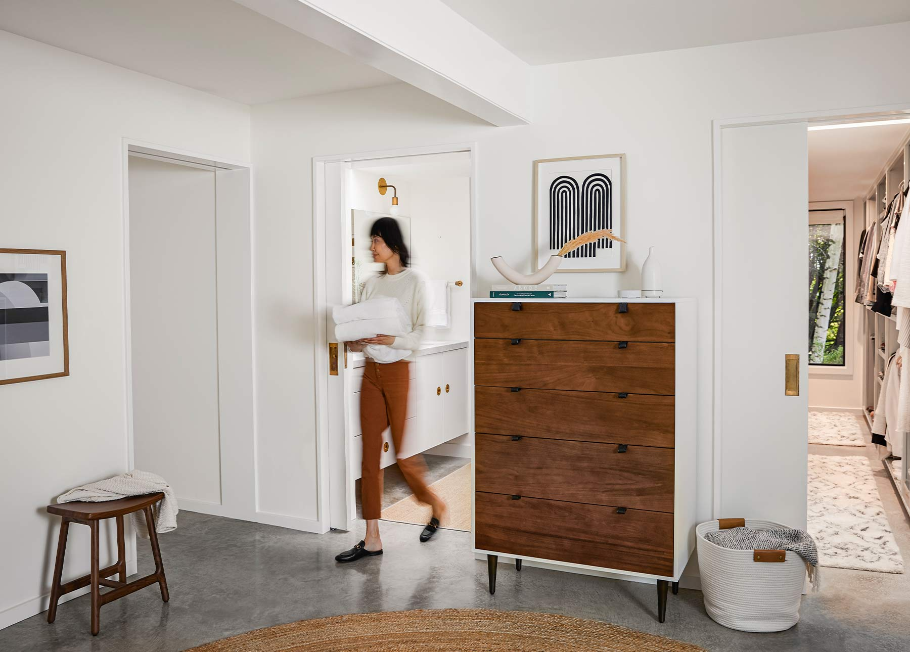 A tall Envelo Dresser in a white room with a woman walking by.