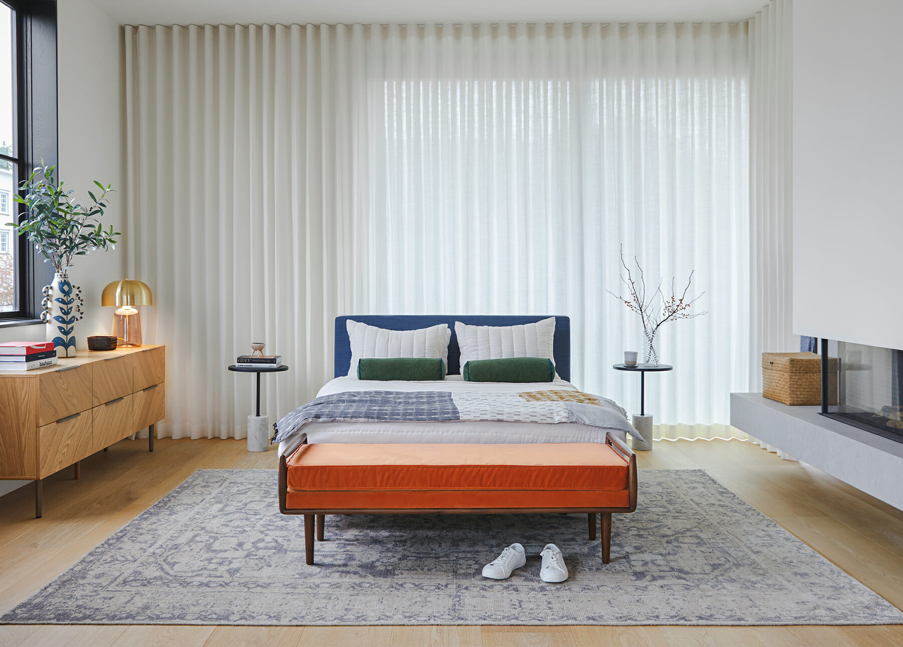 A bedroom is shown with a bright orange bench, neutral rug, and blue bedding.