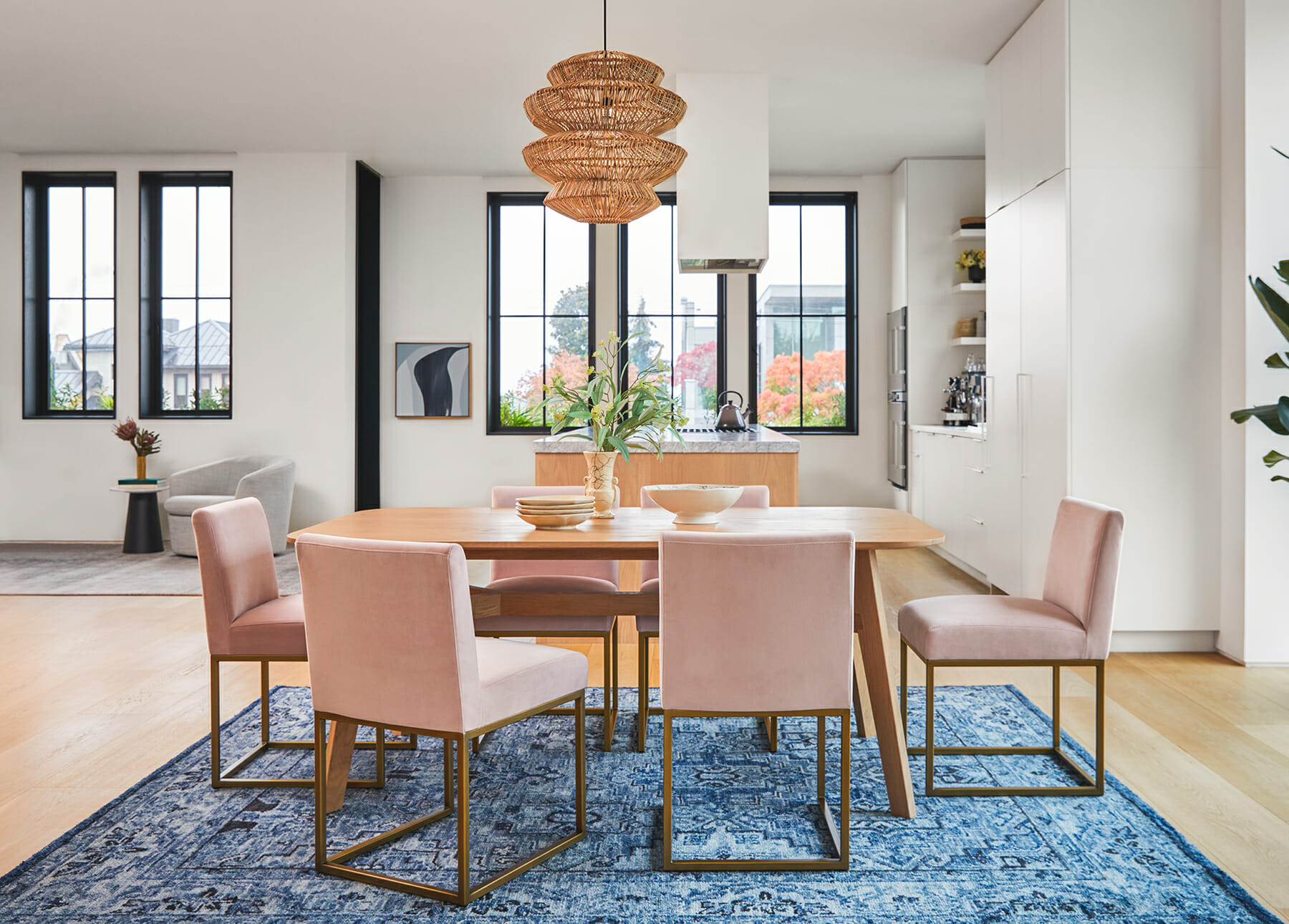 The blue Zakra Rug is shown with light pink Oscuro dining chairs.