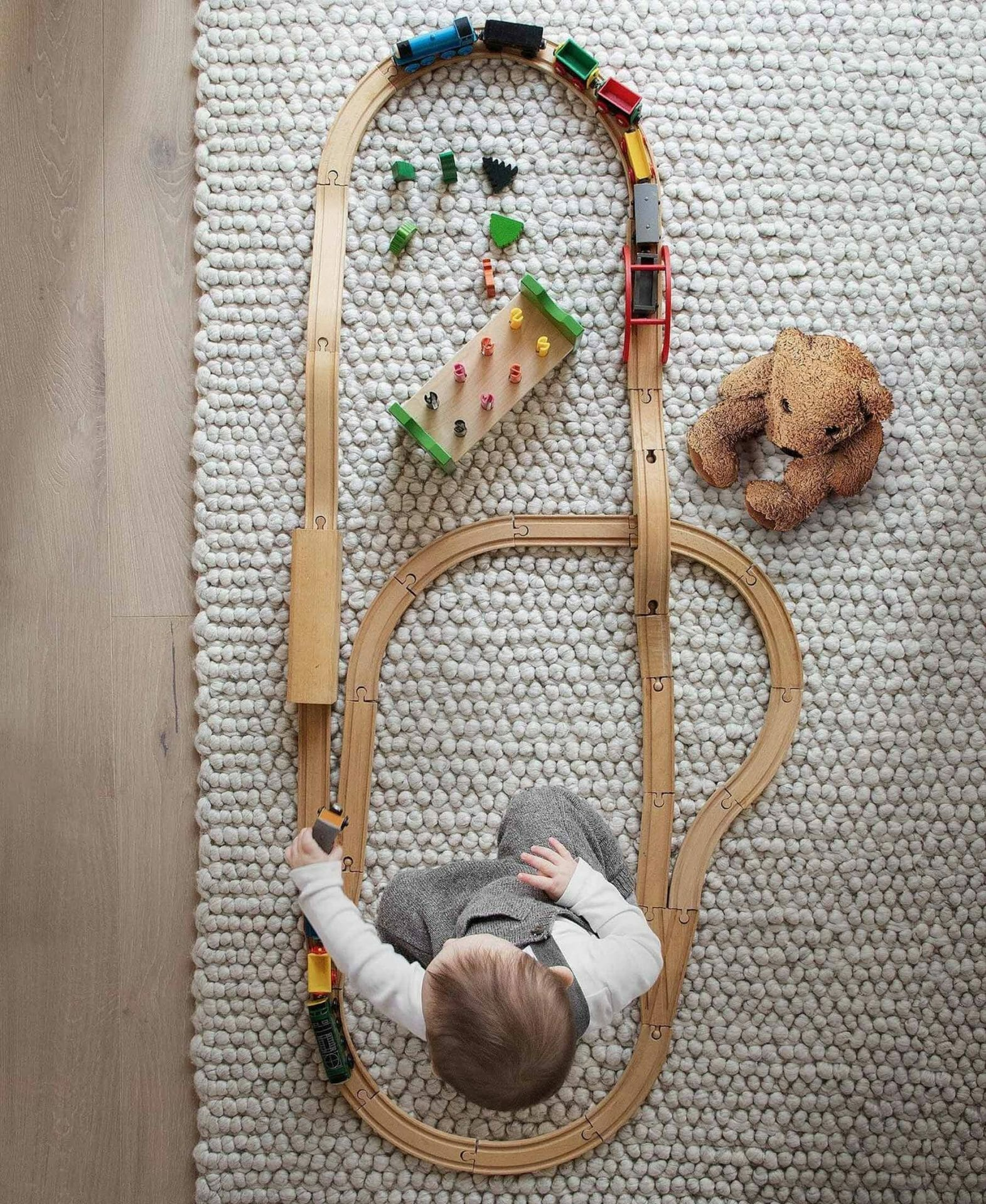 Phil Cohen's son plays with a wooden train track on the wool Hira Rug by Article.