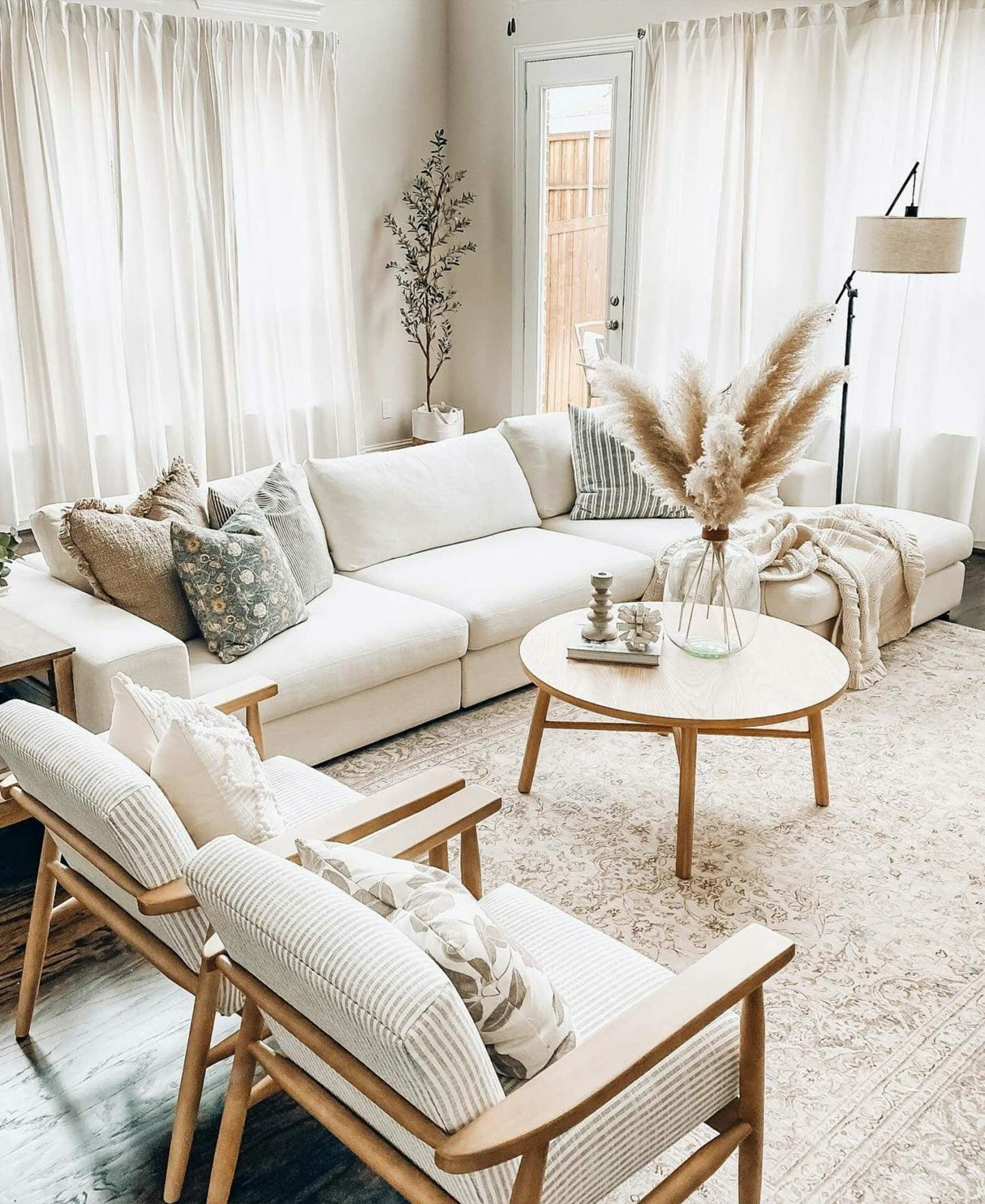 A white sectional sofa and two white armchairs are shown with pampas grass.