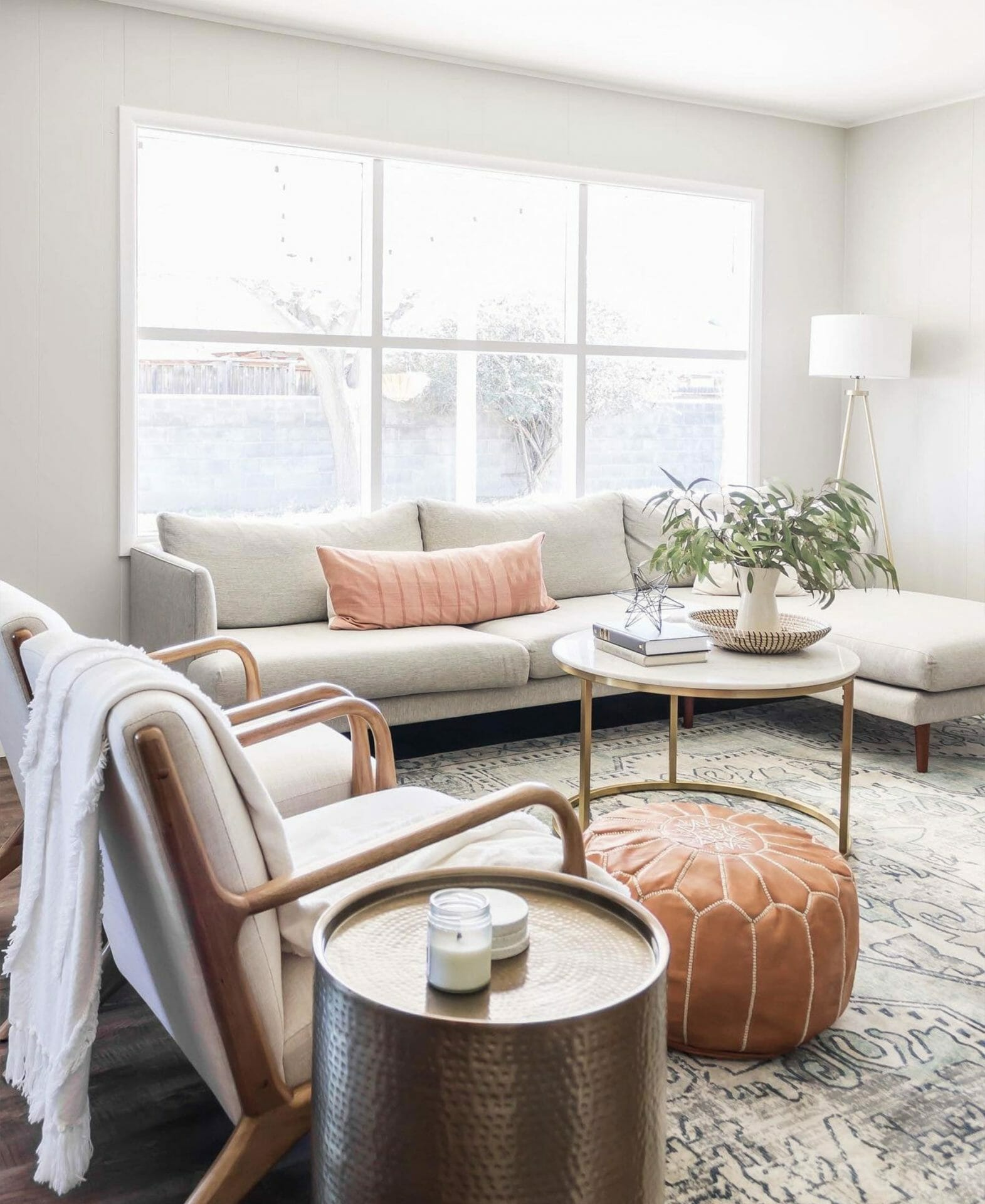A gray sectional sofa sits in front of a large window in this bright space.
