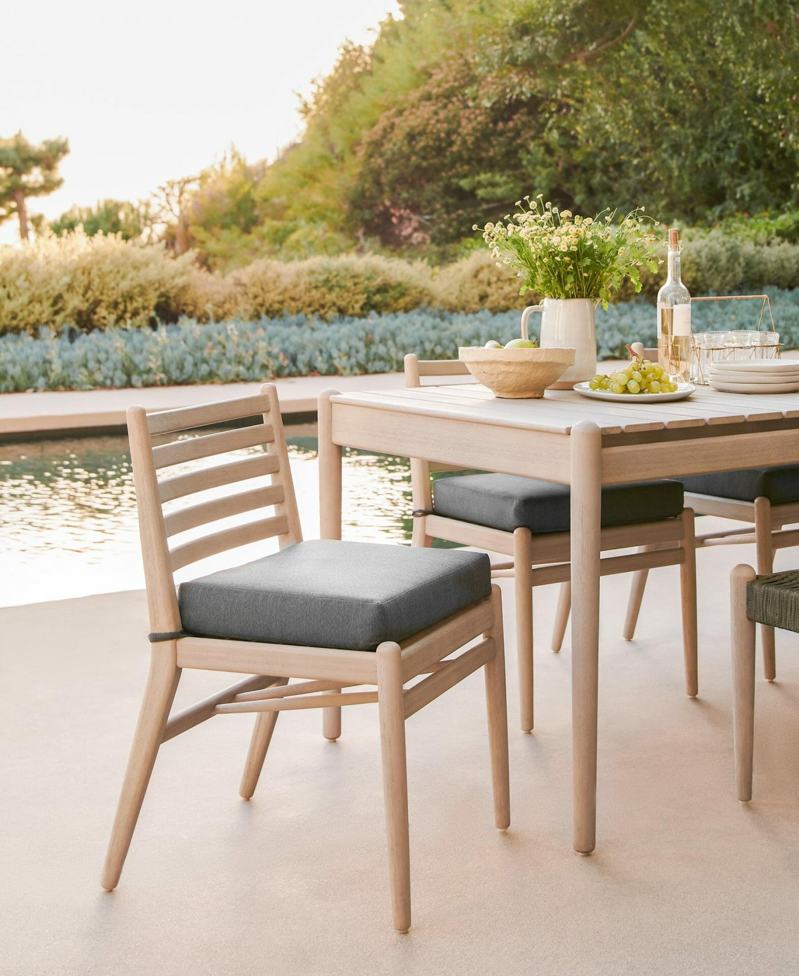 The Lagora Dining Table and Chairs are seen poolside.