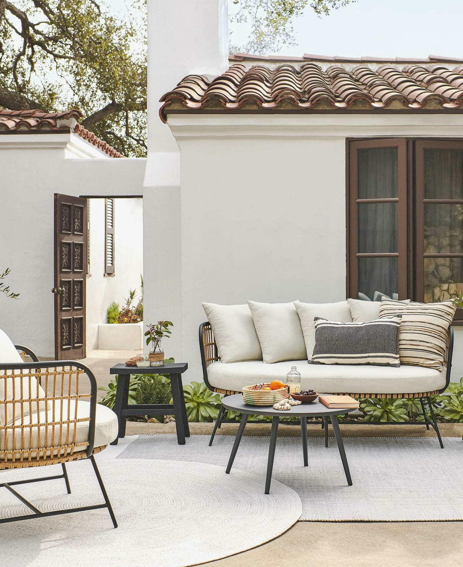 The Onya Sofa is featured in a condo courtyard with Spanish-style architecture.