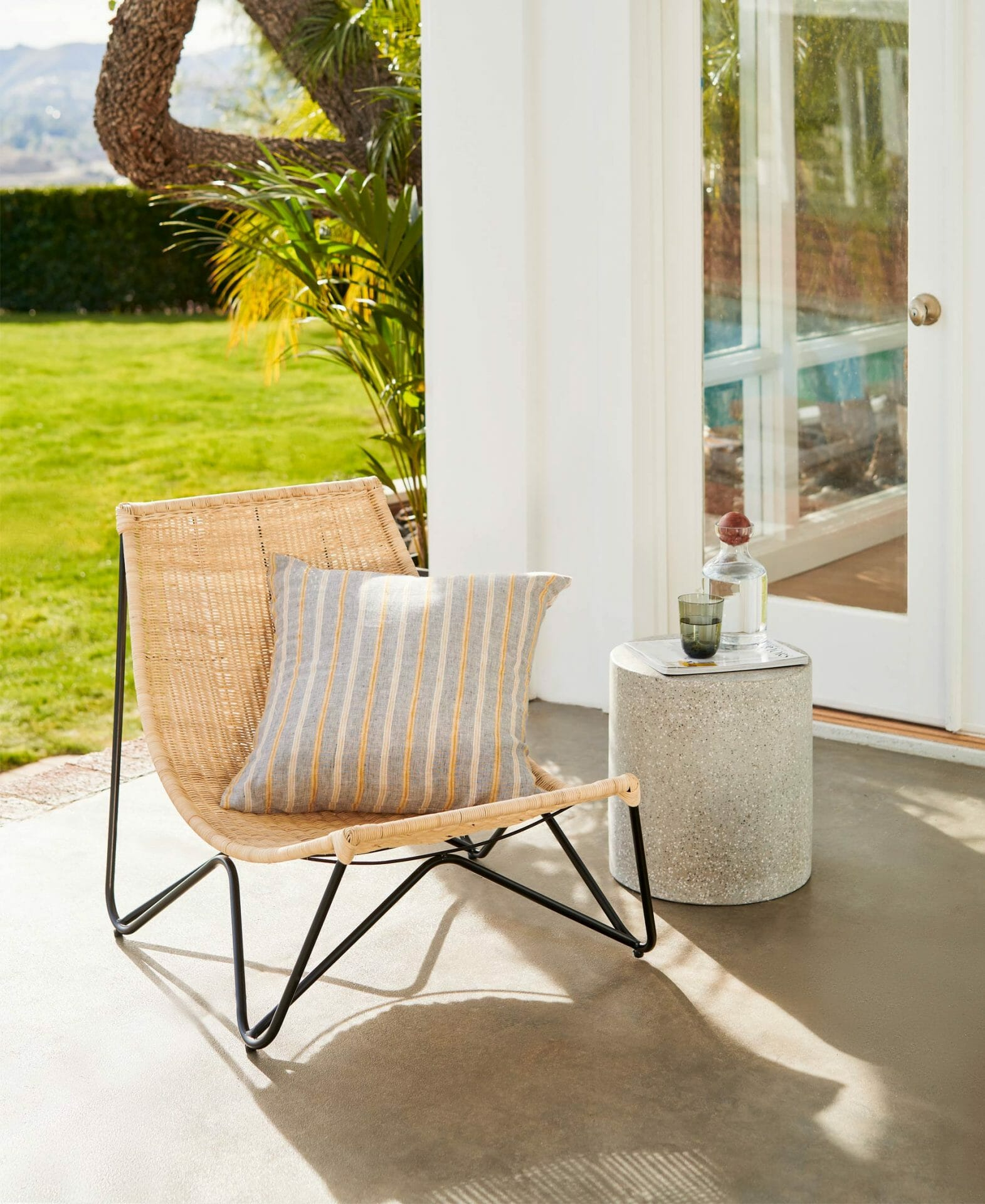 The rattan Ikast Lounge Chair is shown with an accent pillow and side table.