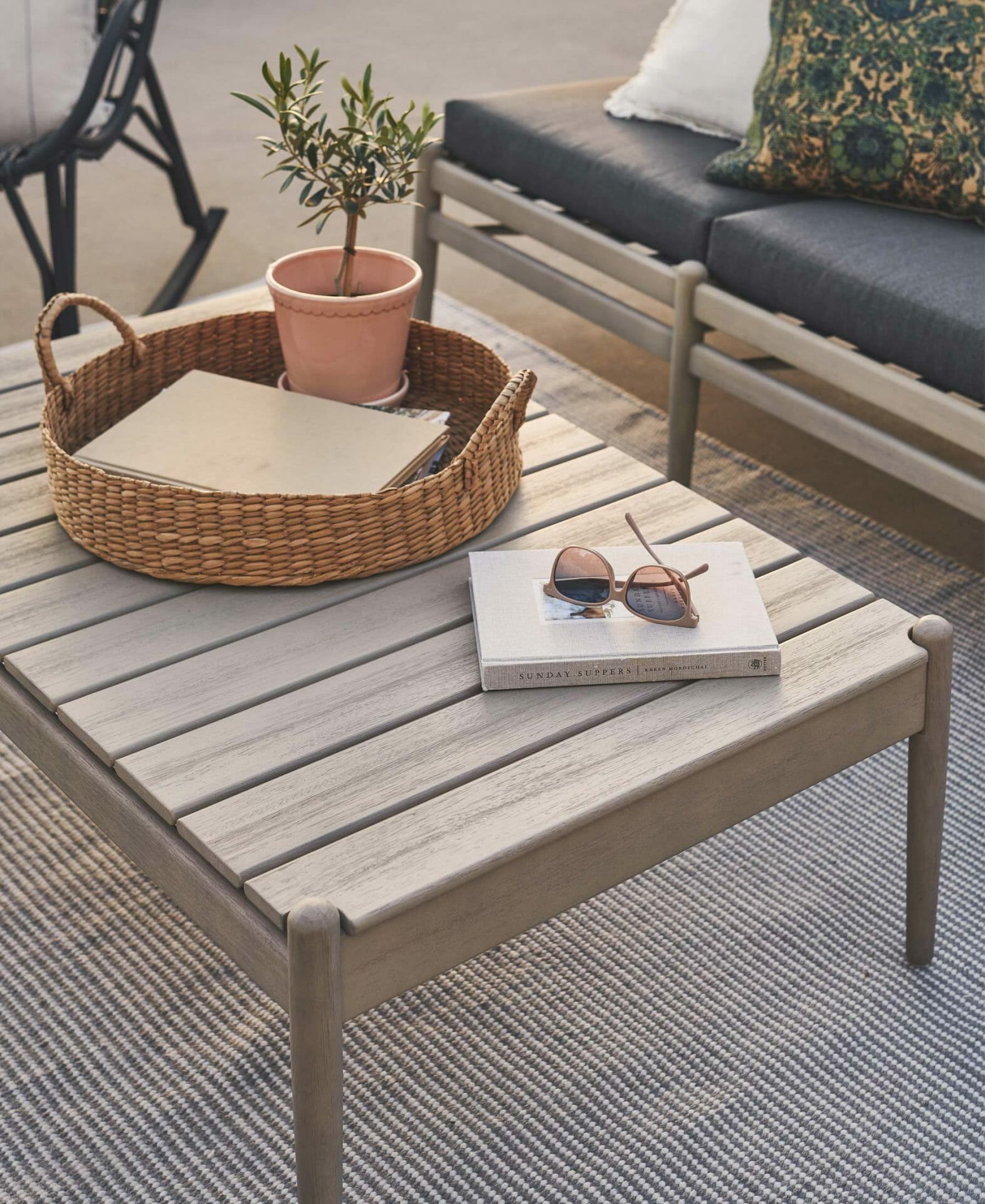 The eucalyptus Lagora Coffee Table is shown with a rattan tray with potted plant, and notebook with sunglasses.