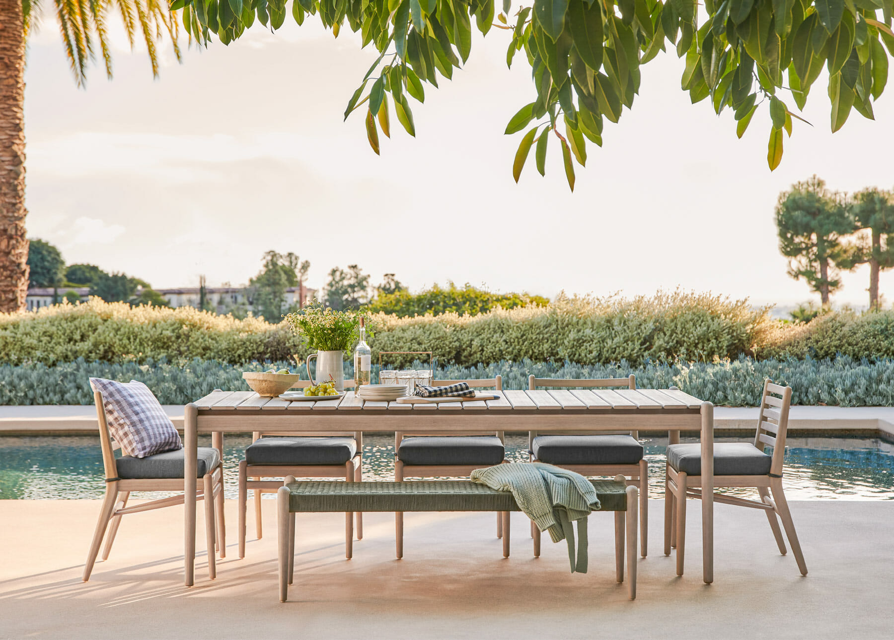 Article's eucalyptus Lagora Collection is shown poolside with various greenery surrounding it.
