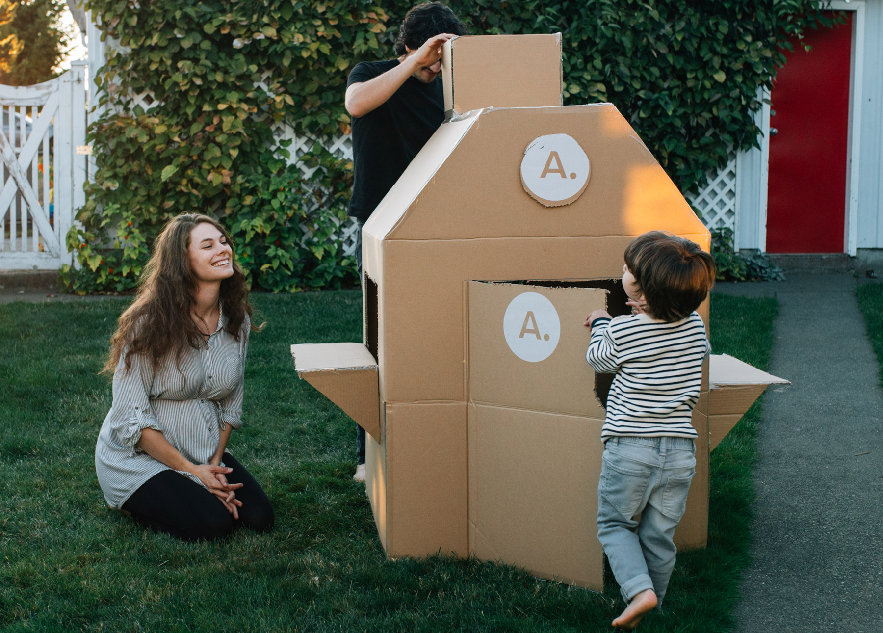 A family enjoys playing with a cardboard box fort. There are awesome details like a chimney, door, and window ledges.