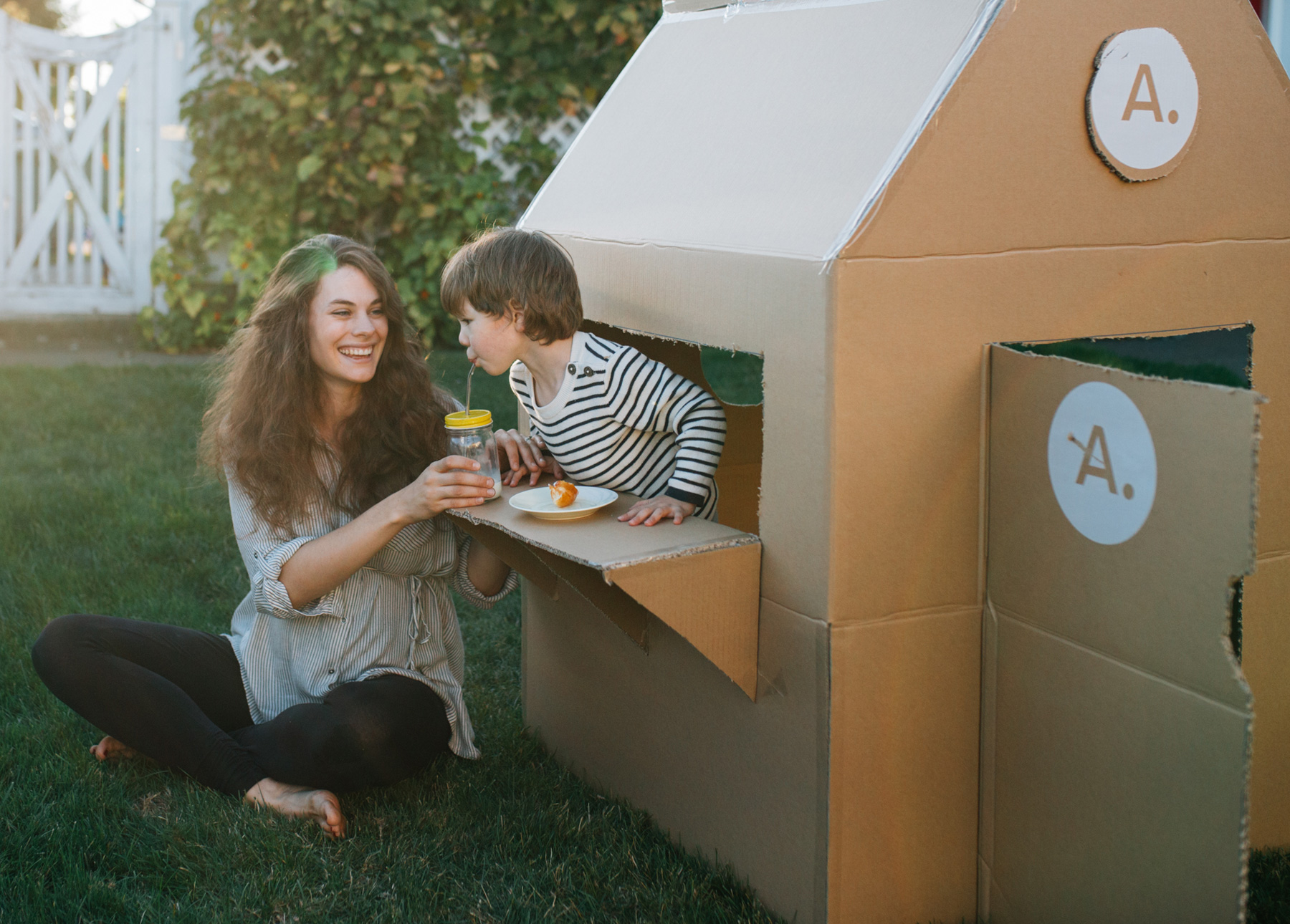 A mother and son enjoy playing with a cardboard box fort.