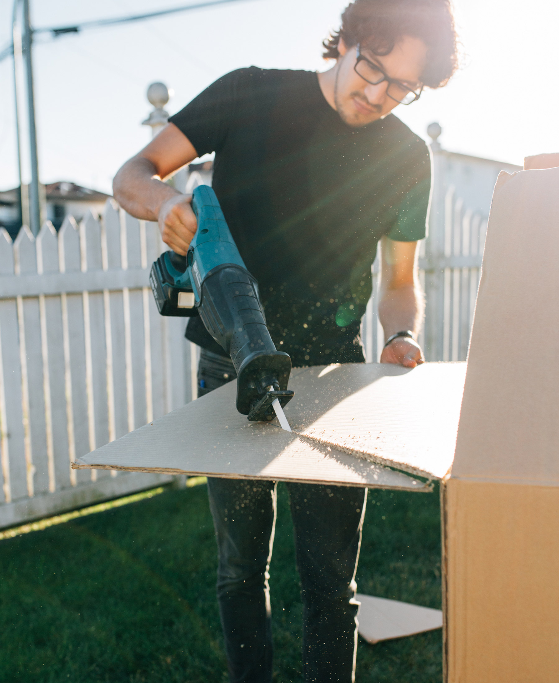 Jorge cuts into a cardboard box using a reciprocating saw to create pieces for a box fort.