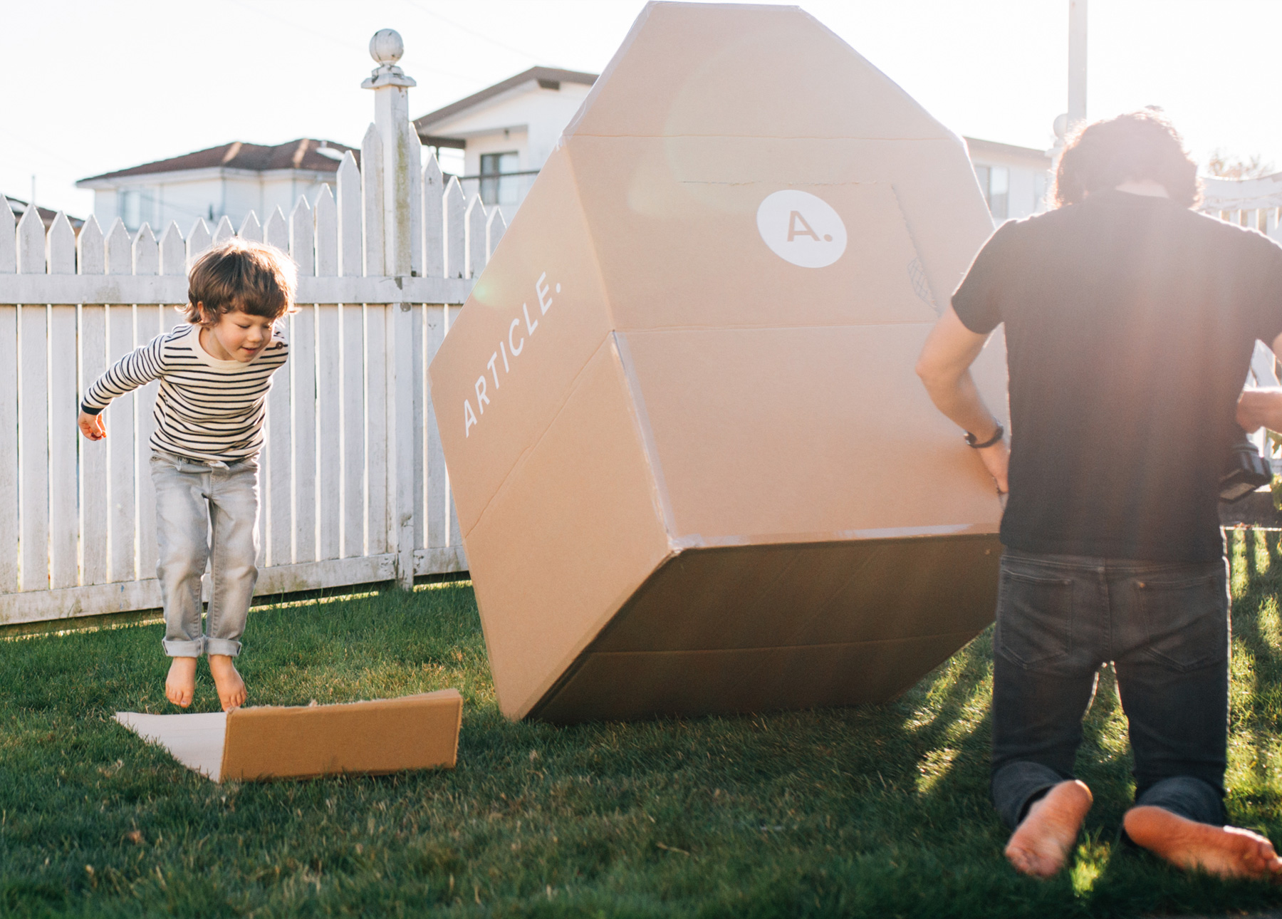 A father and son work together to create a cardboard box fort