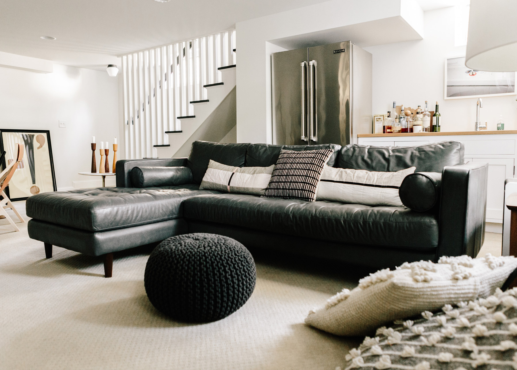 A gray leather sectional makes a basement suite look more cozy.