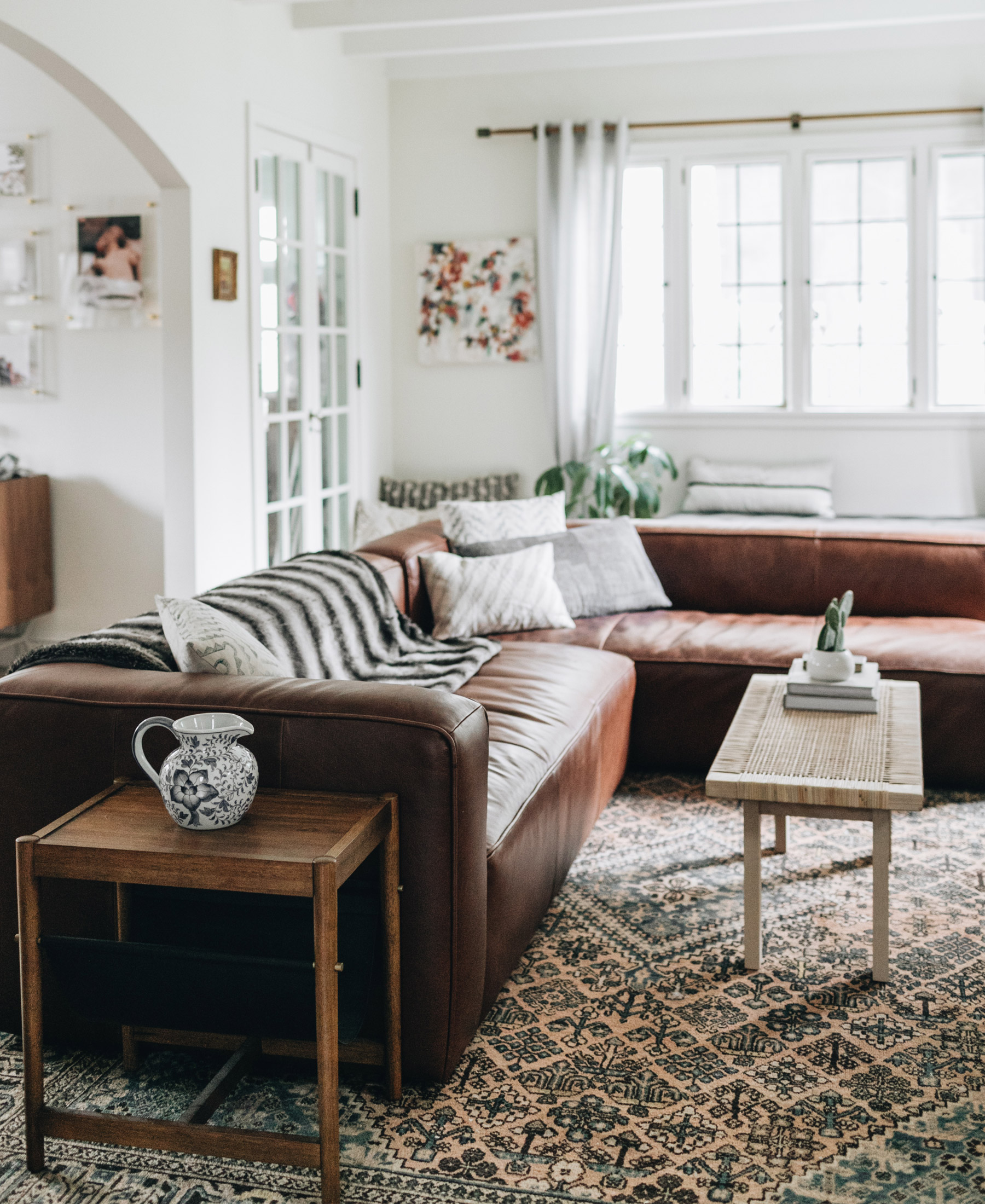 A rich, brown leather sectional adds richness to a white living room.