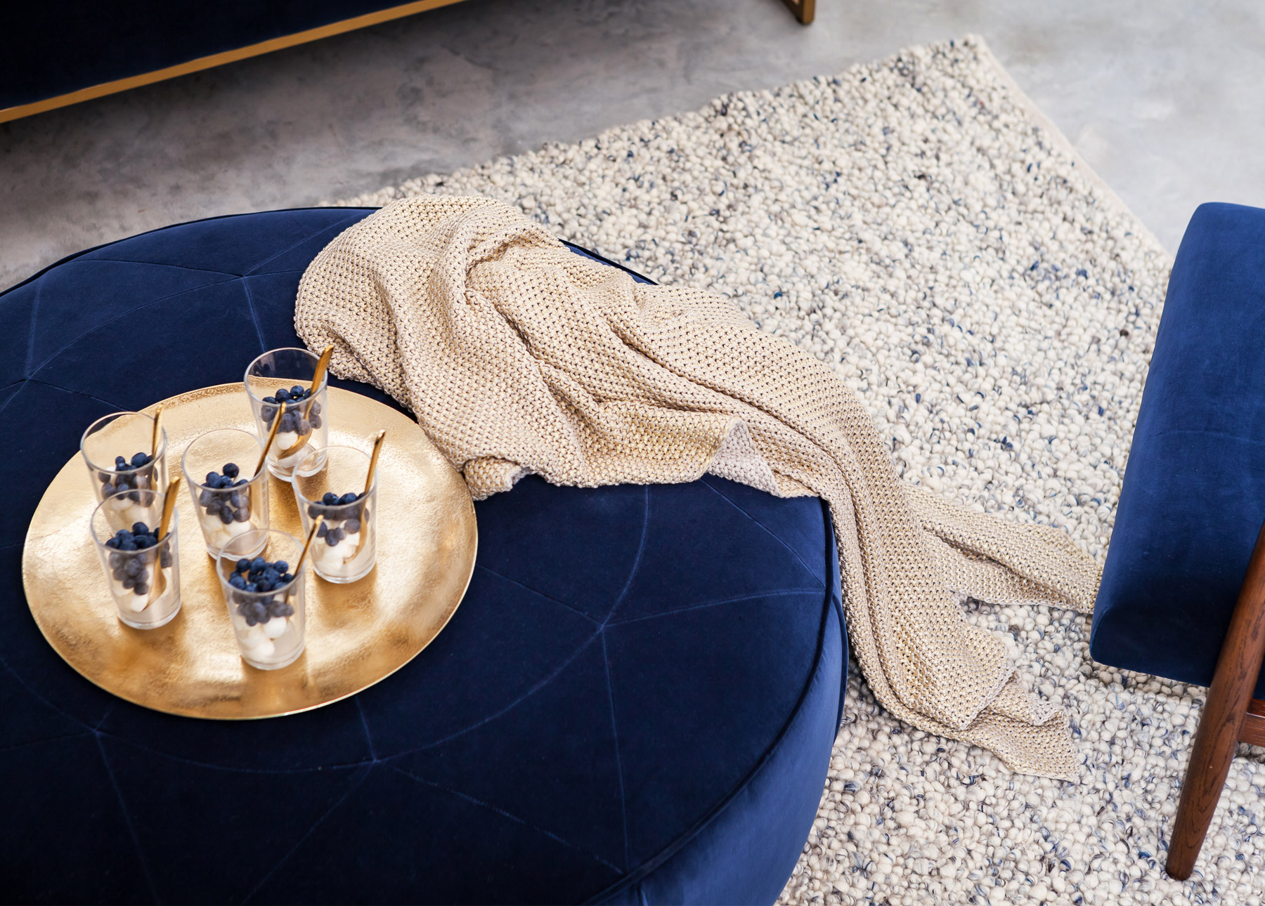 A blue velvet ottoman styled with a gold throw and gold platter.