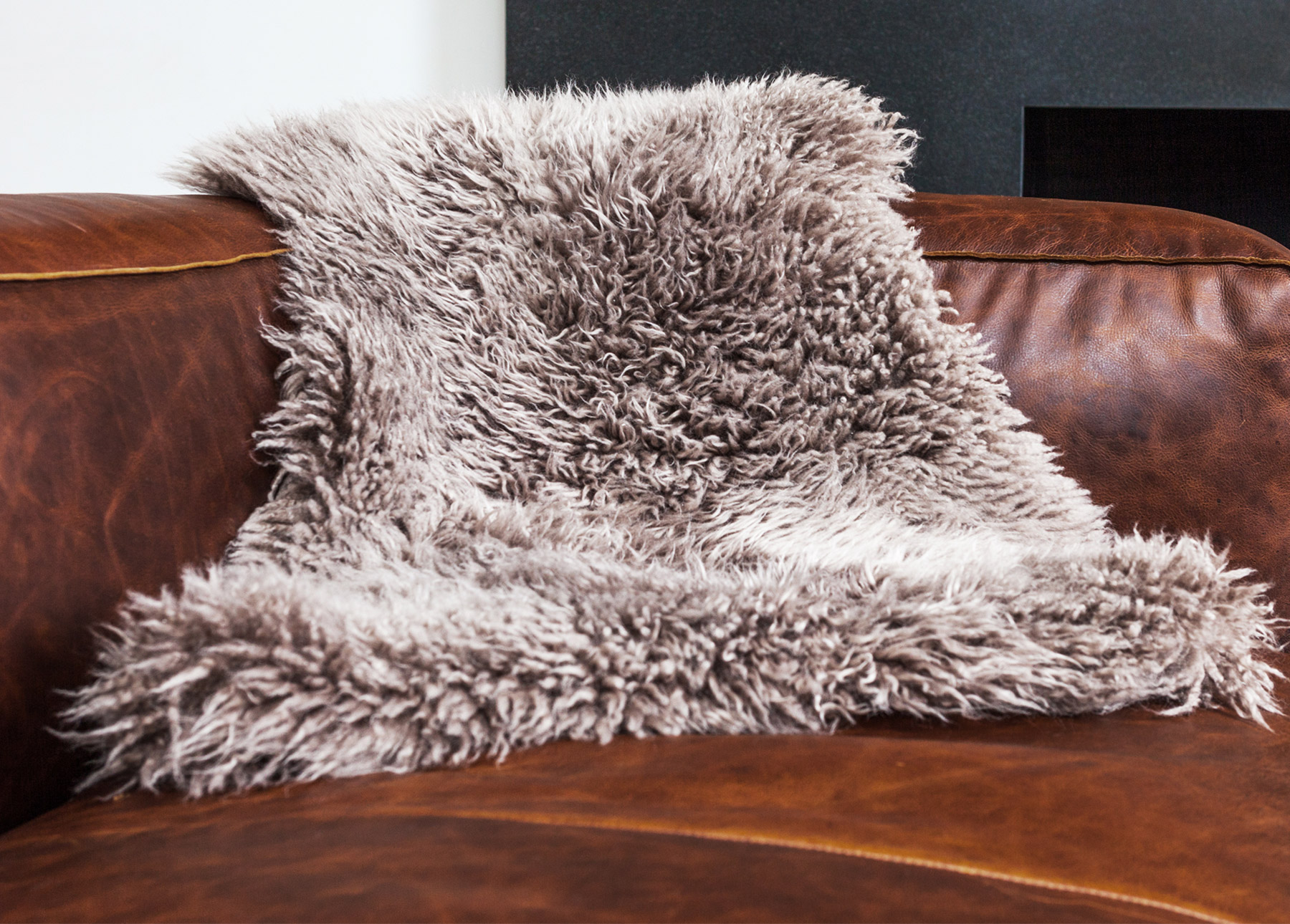 Lana Gray Sheepskin Throw on a Cigar Rawhide Brown leather sofa