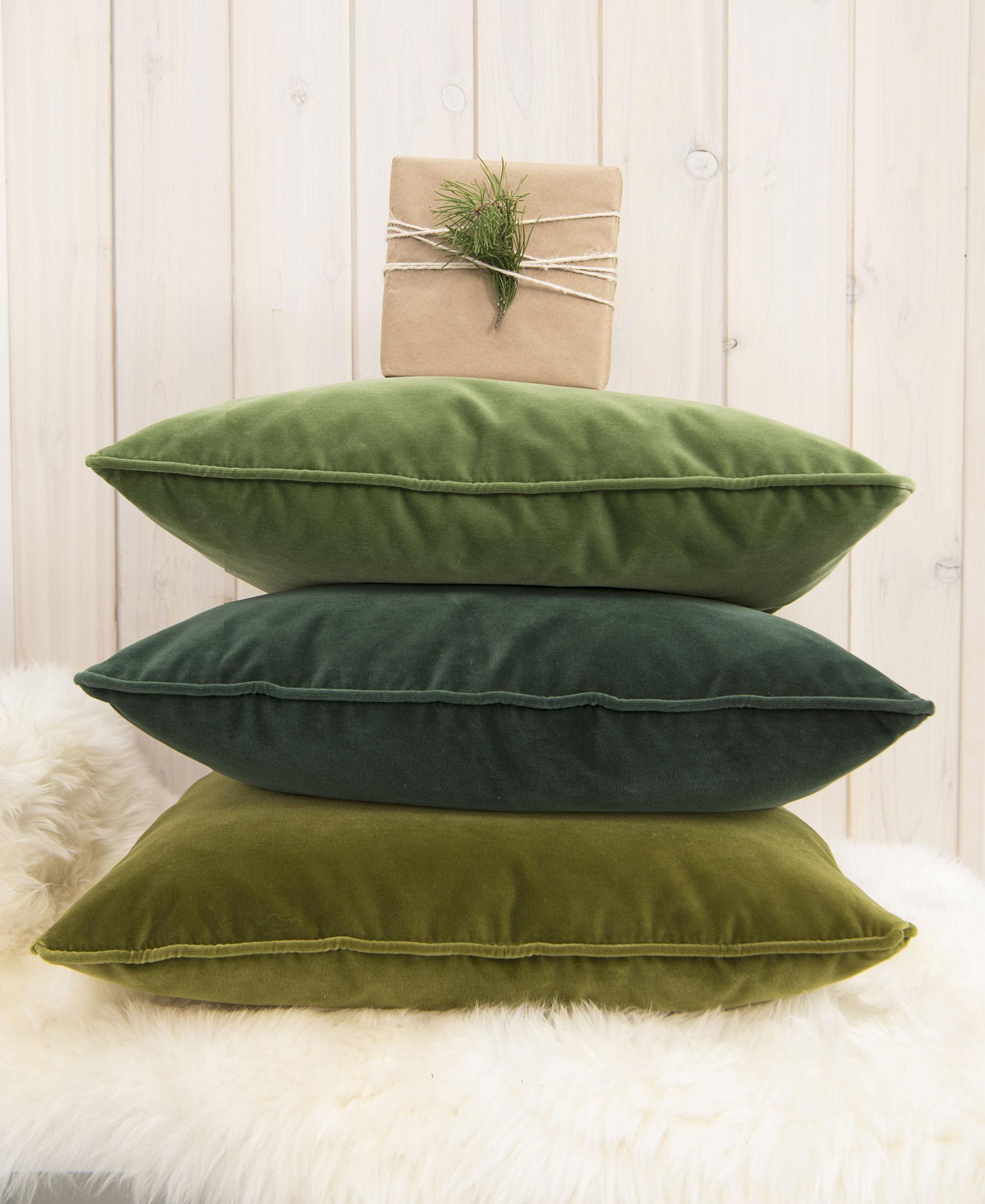 Stacked green velvet pillows.