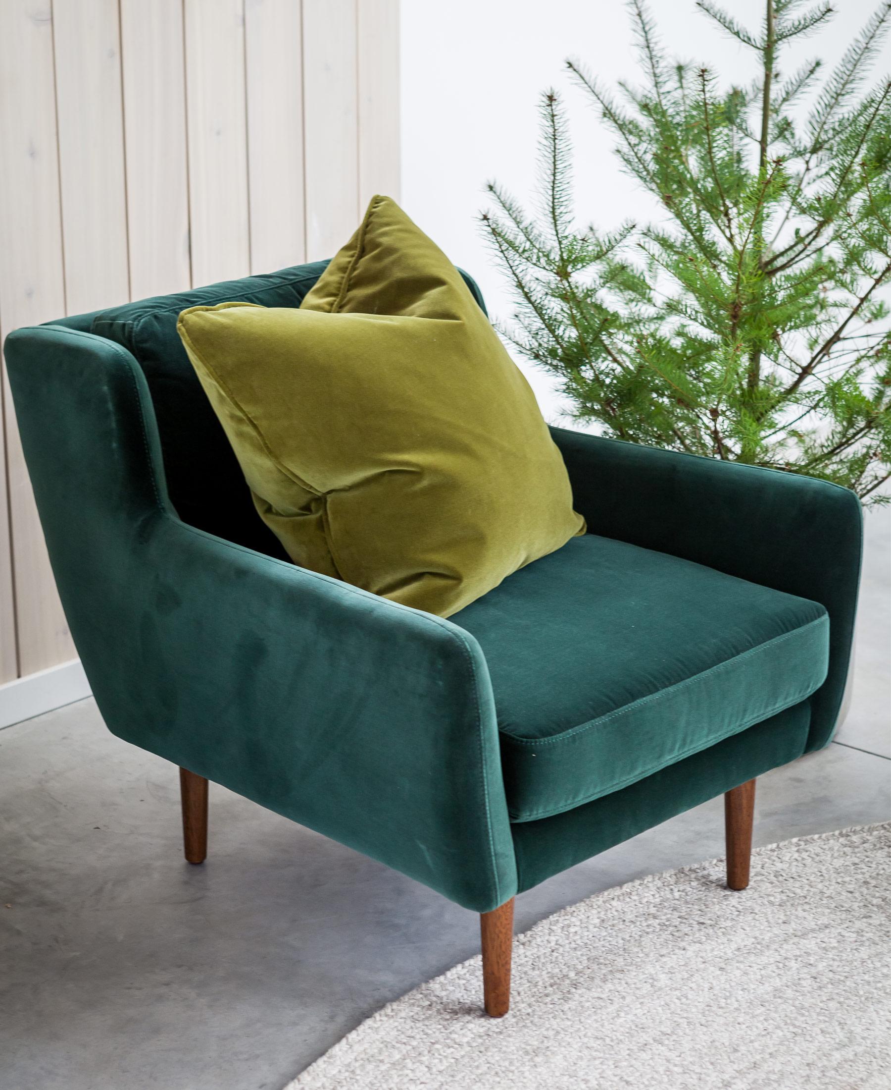 Green velvet pillow on a green velvet armchair.