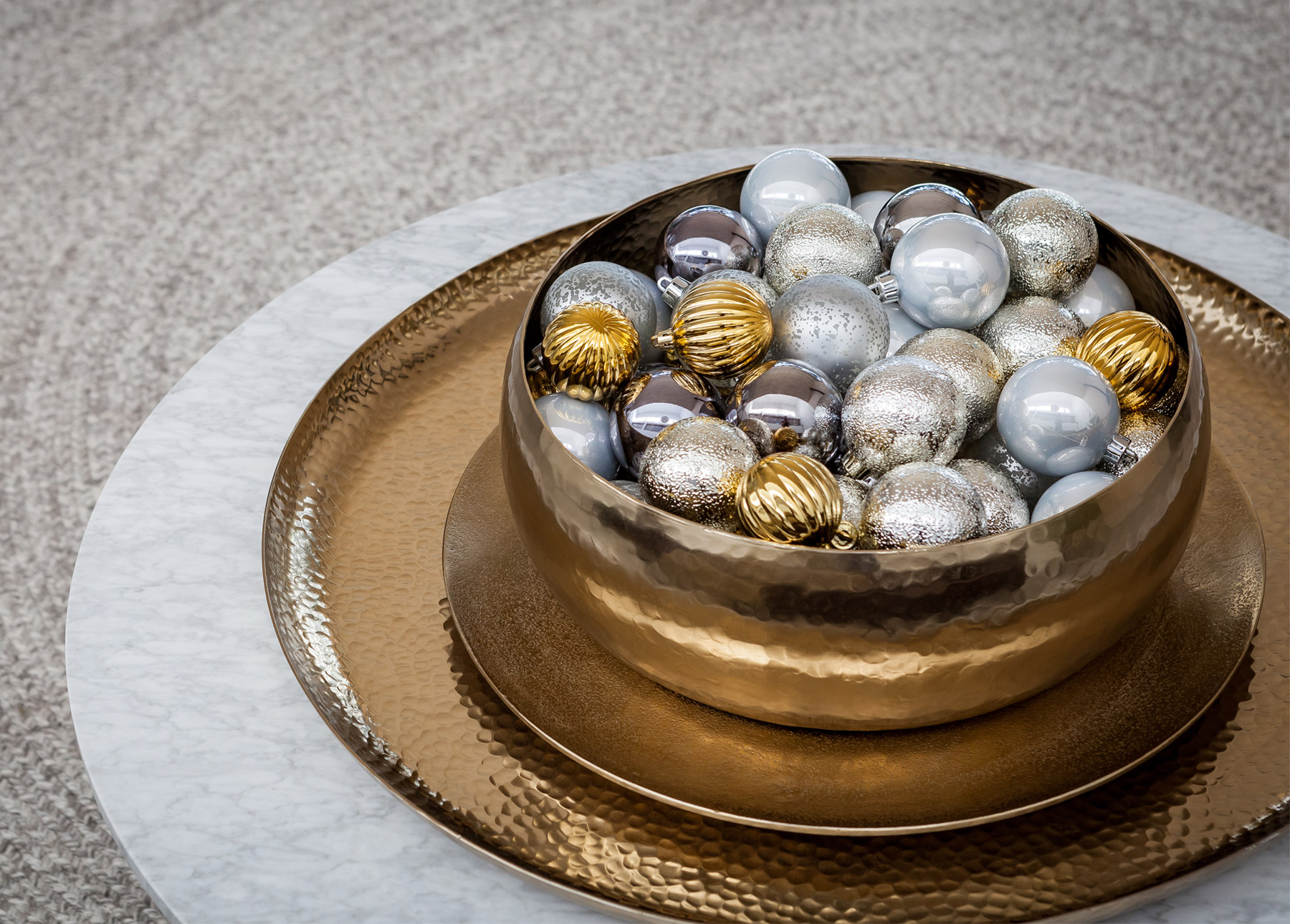 Holiday ornaments fill a shimmering metallic bowl.