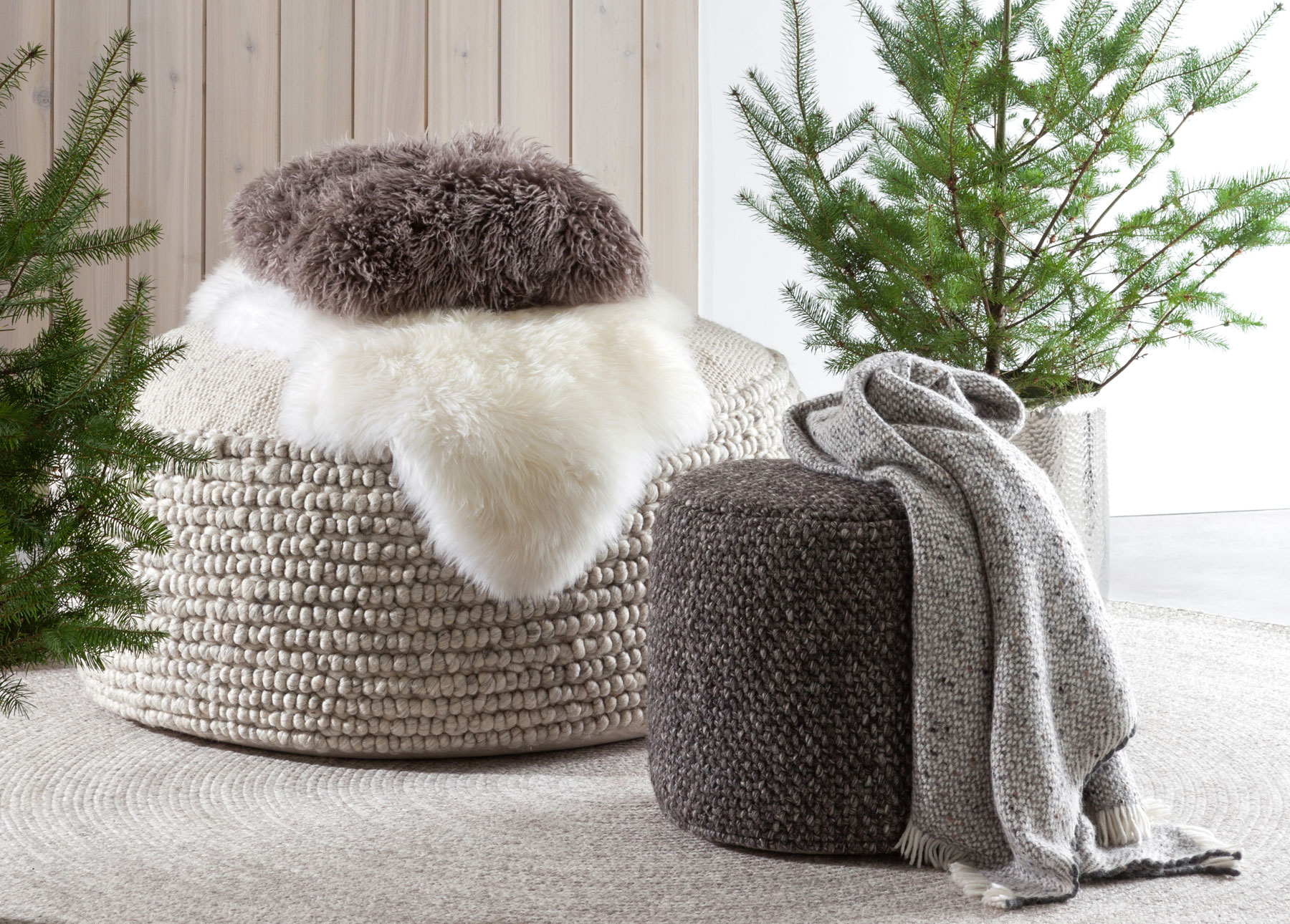 Soft textures like sheepskins, wool throws, and poufs make a living room cozy.