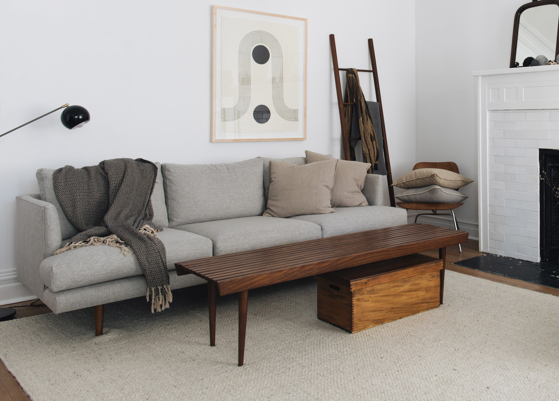 A mid-century modern gray sofa sits on a creamy wool rug.