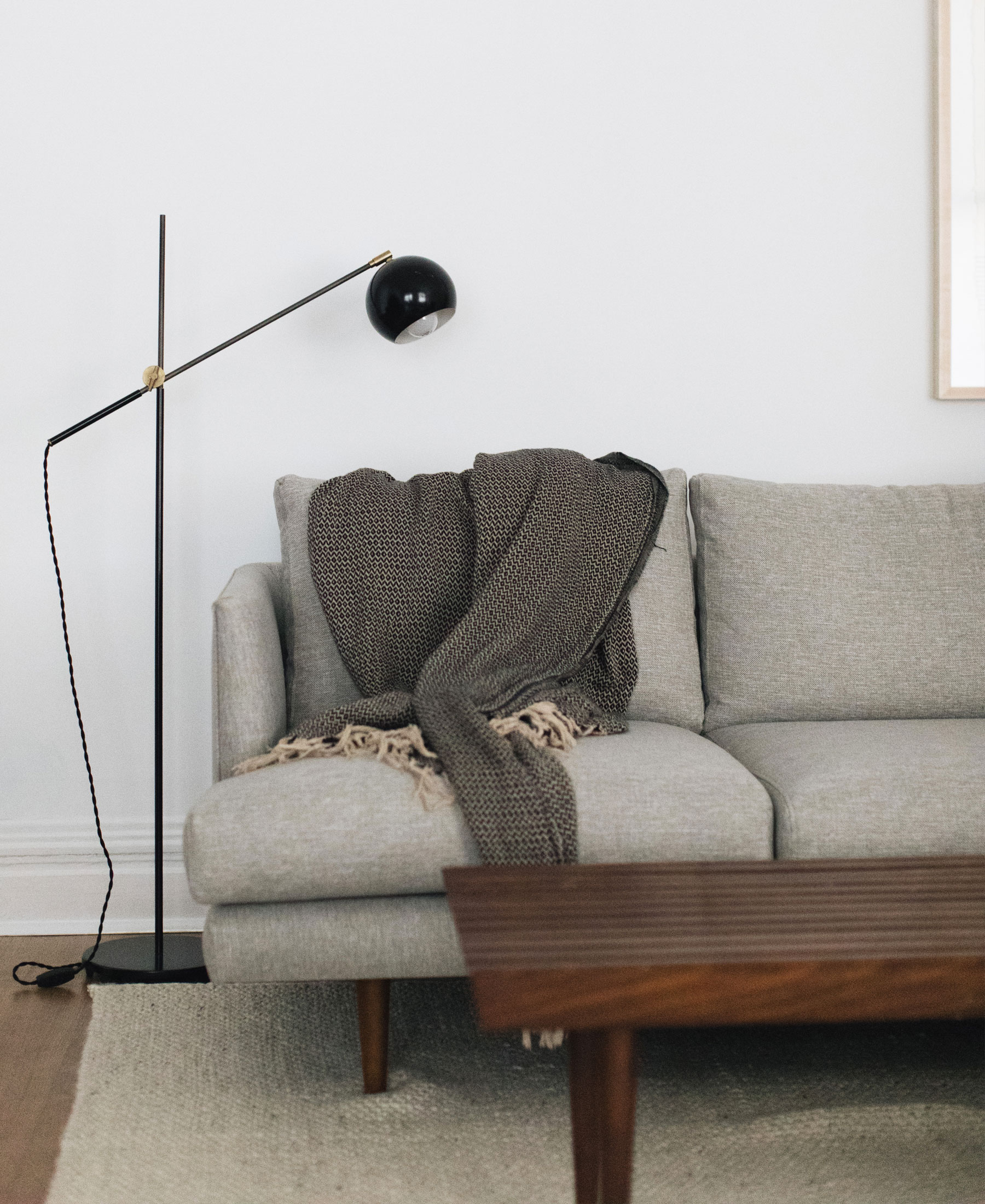 Angular mid-century modern lighting and a gray sofa.